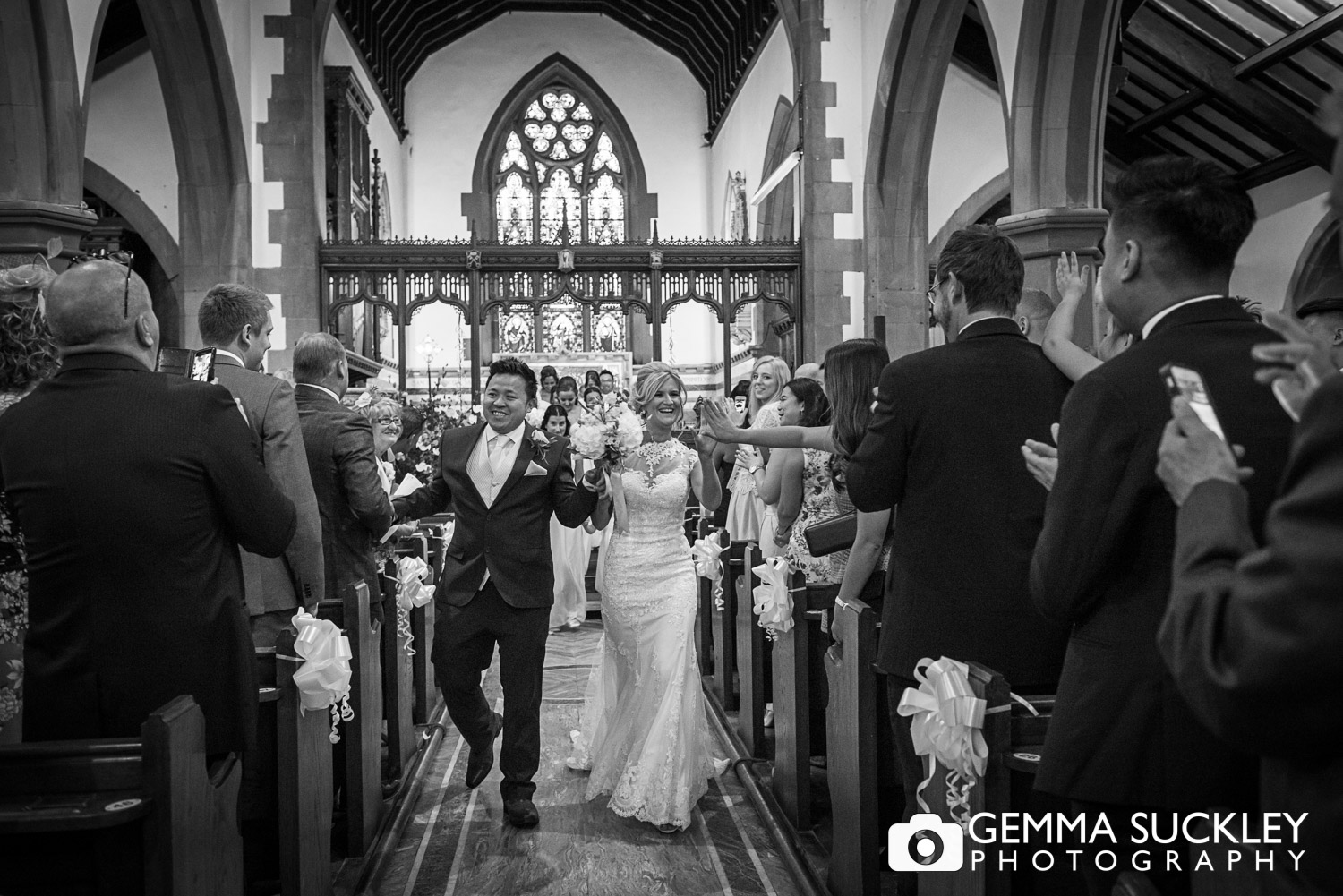 bride and groom high fiving their wedding guests walking out the church