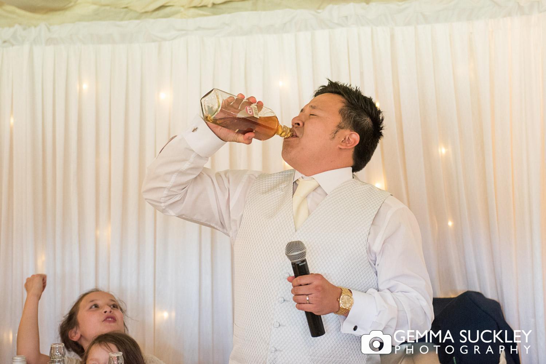 Groom drinking Whiskey at The Moorlands Inn