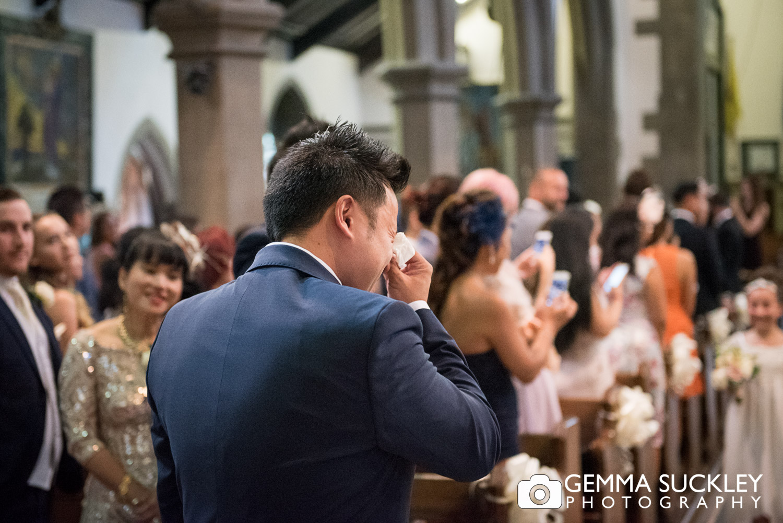 Groom crying as the flower girls walk down the church aisle
