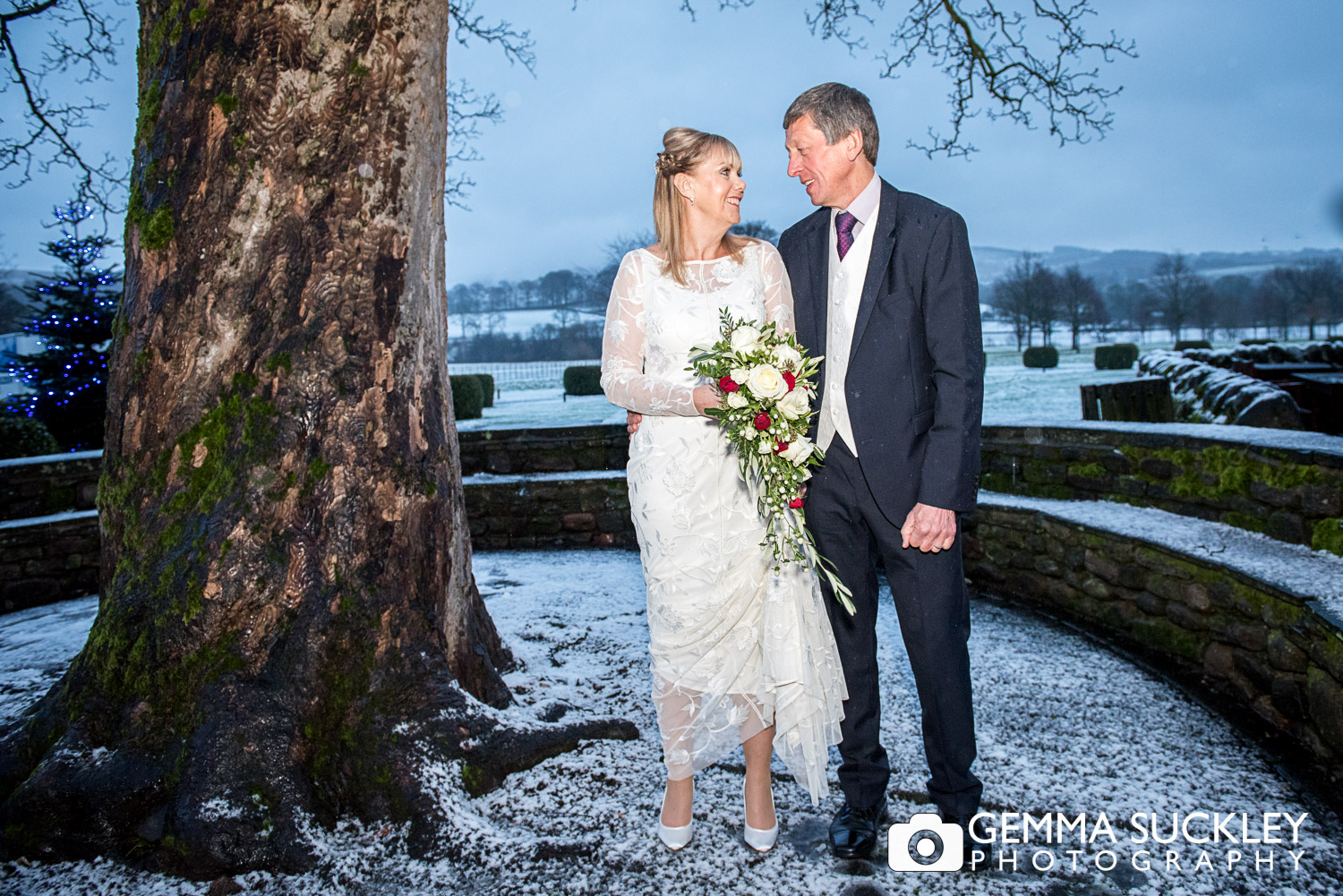 bride and groom in the snow outside The Devonshire arms in bolton Abbey