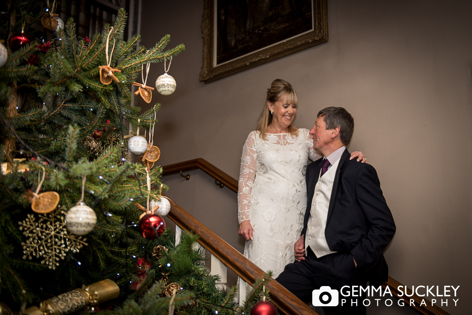 bride and groom stood by a Christmas tree in The Devonshire arms in bolton Abbey
