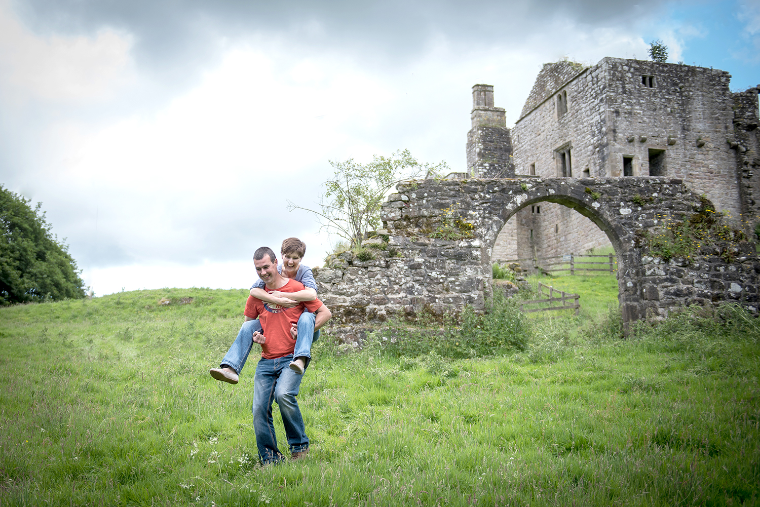 man carrying his fiancée at barden town in bolton abbey during engagement photo shoot