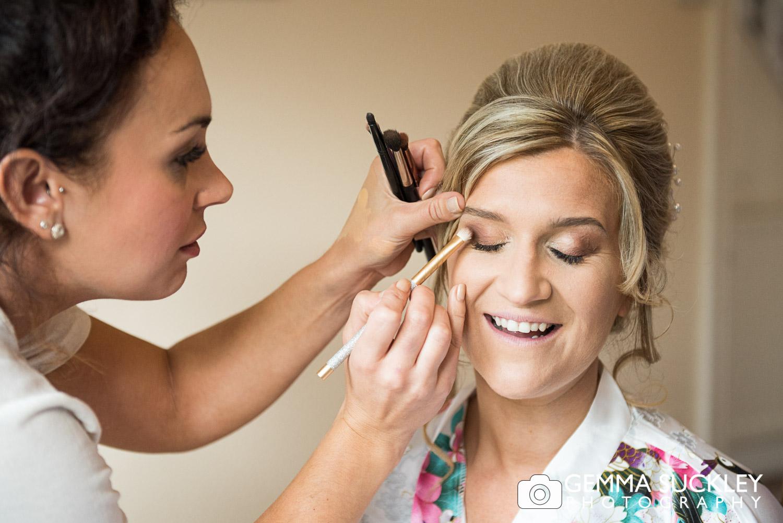 bride getting get her make up done during bridal prep