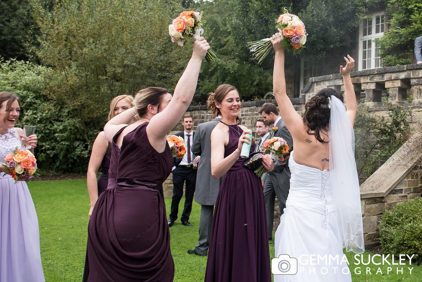 bride and bridesmaids at outdoor wedding spaying deodorant