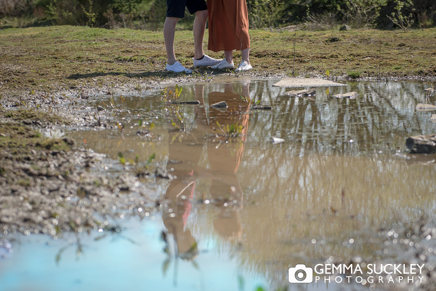 couples feet reflecting in a puddle