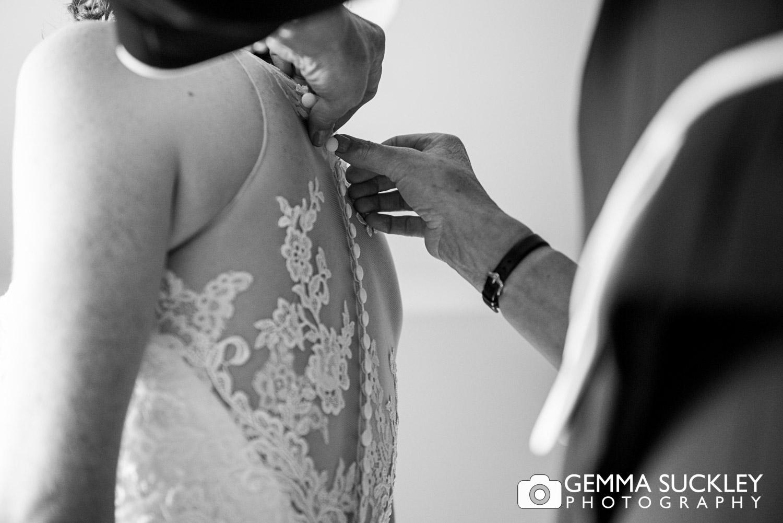 Harrogate bride getting into her wedding dress
