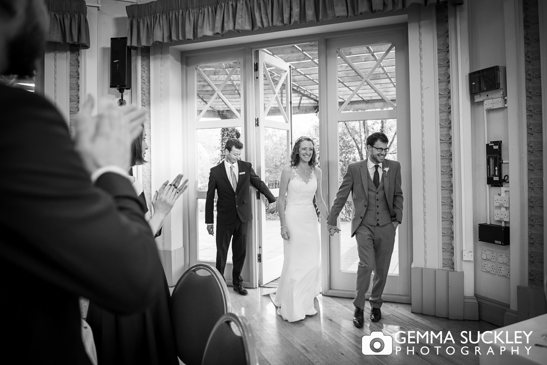 bride and groom walking through the sun pavilion doors in harrogate wedding venue
