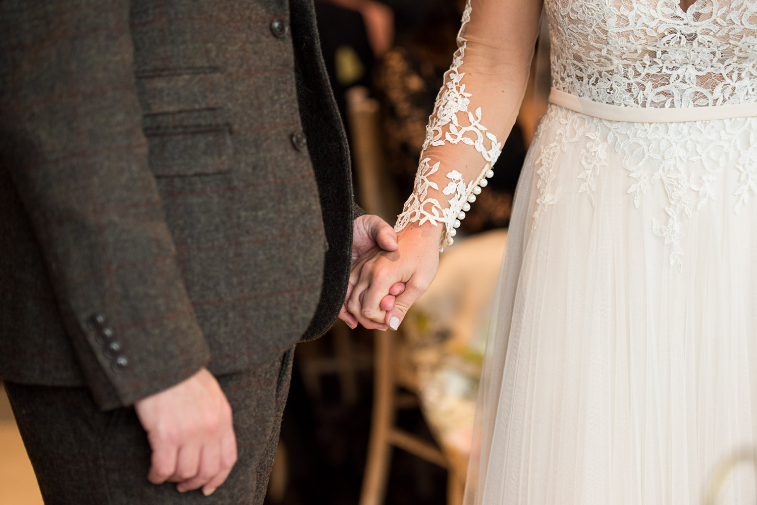 bride and groom holding hands during the wedding ceremony