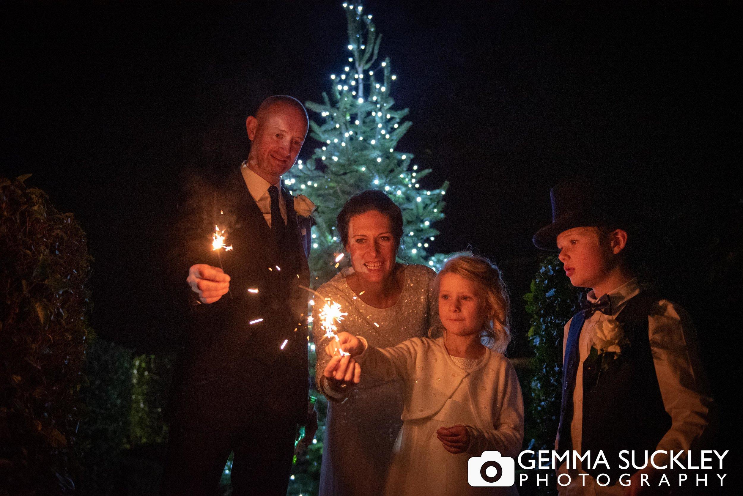 family holding sparklers at christmas wedding at the devonshire arms in bolton abbey