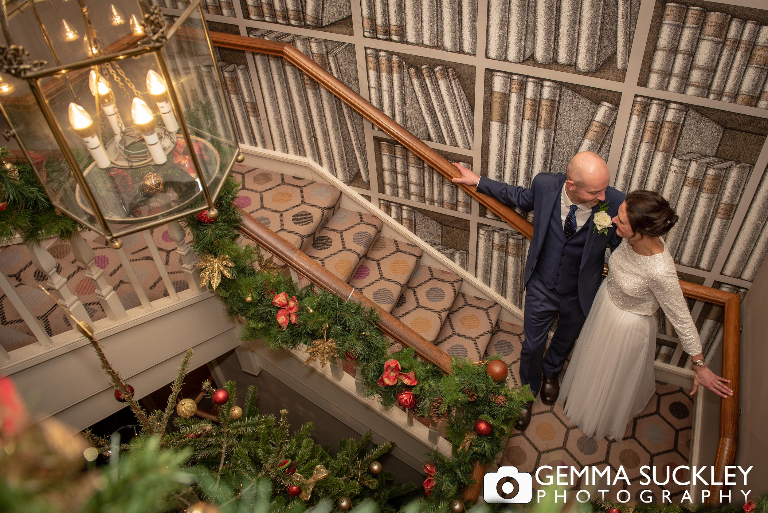 bride and groom on the stairs at the devonshire arms hotel, skipton