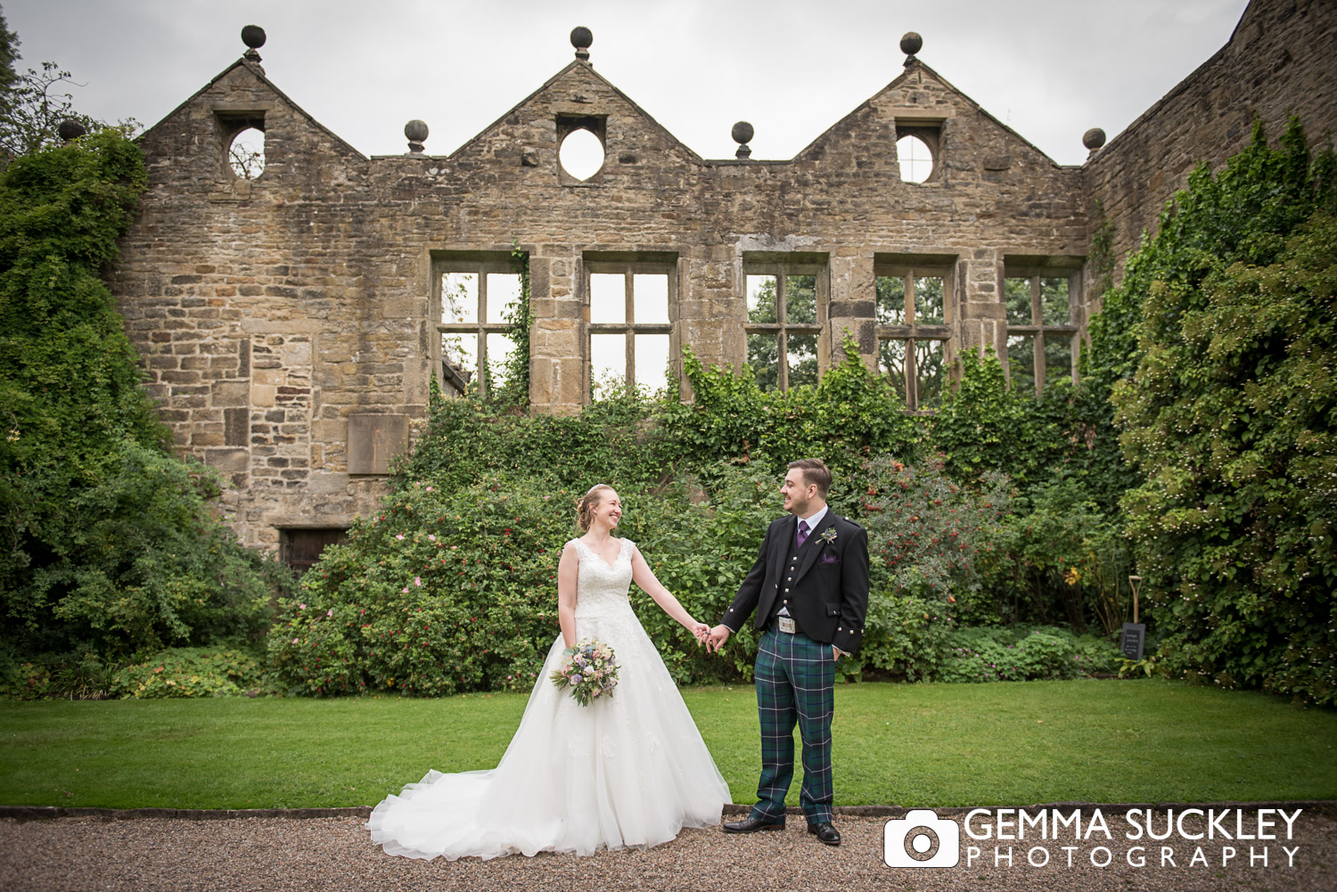 bride and groom holding hands in front of the ruin at east riddlesden hall