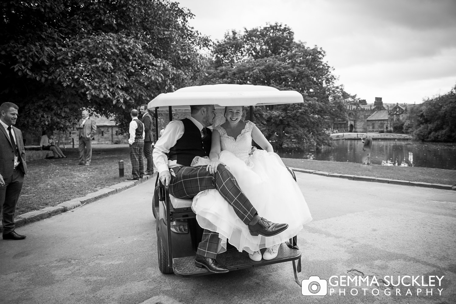 bride and groom in a golf buggy at east riddlesden hall