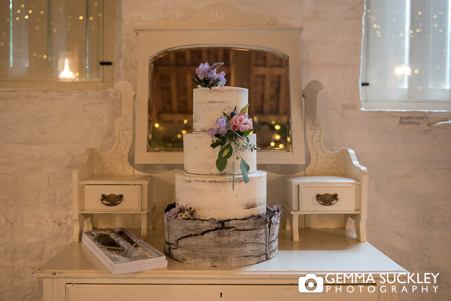 wedding cake on a vintage table in the East riddlesden hall barn