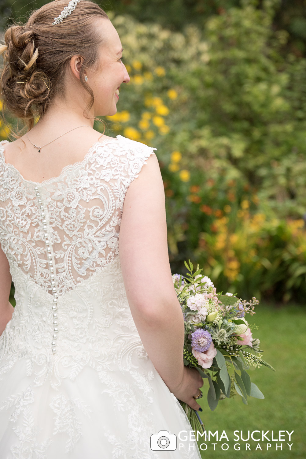 the back of a bride wedding dress detail in the garden at east riddlesden hall