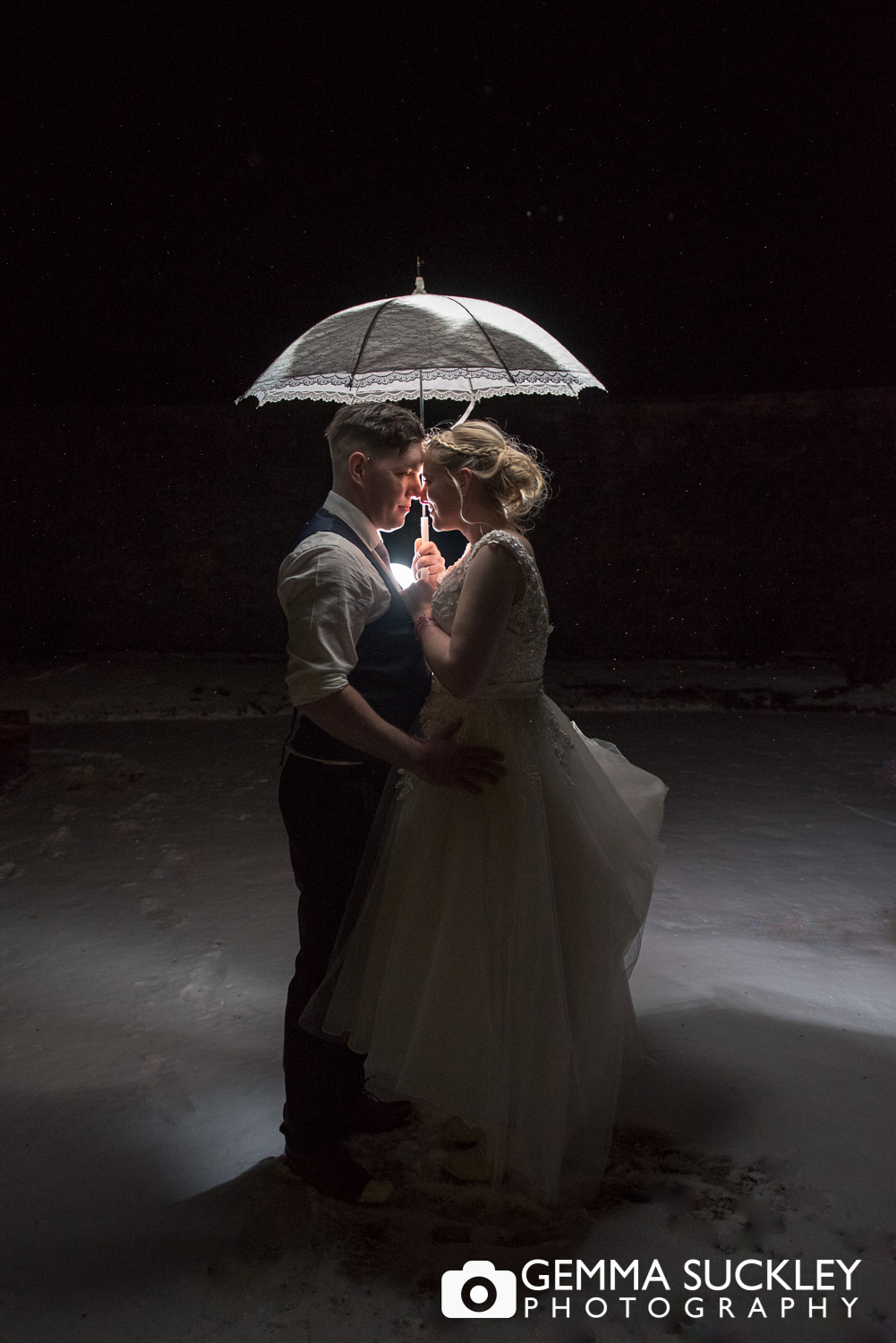 bride and groom under an umbrella outside at Broughton Hall snowy wedding