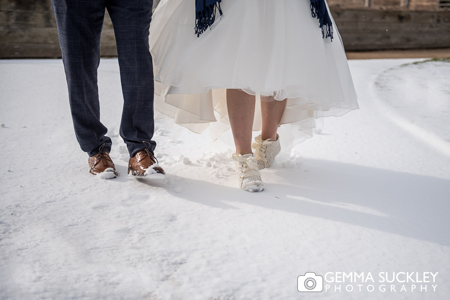 Bride and Groom's feet walking in the snow outside Utopia, Skipton
