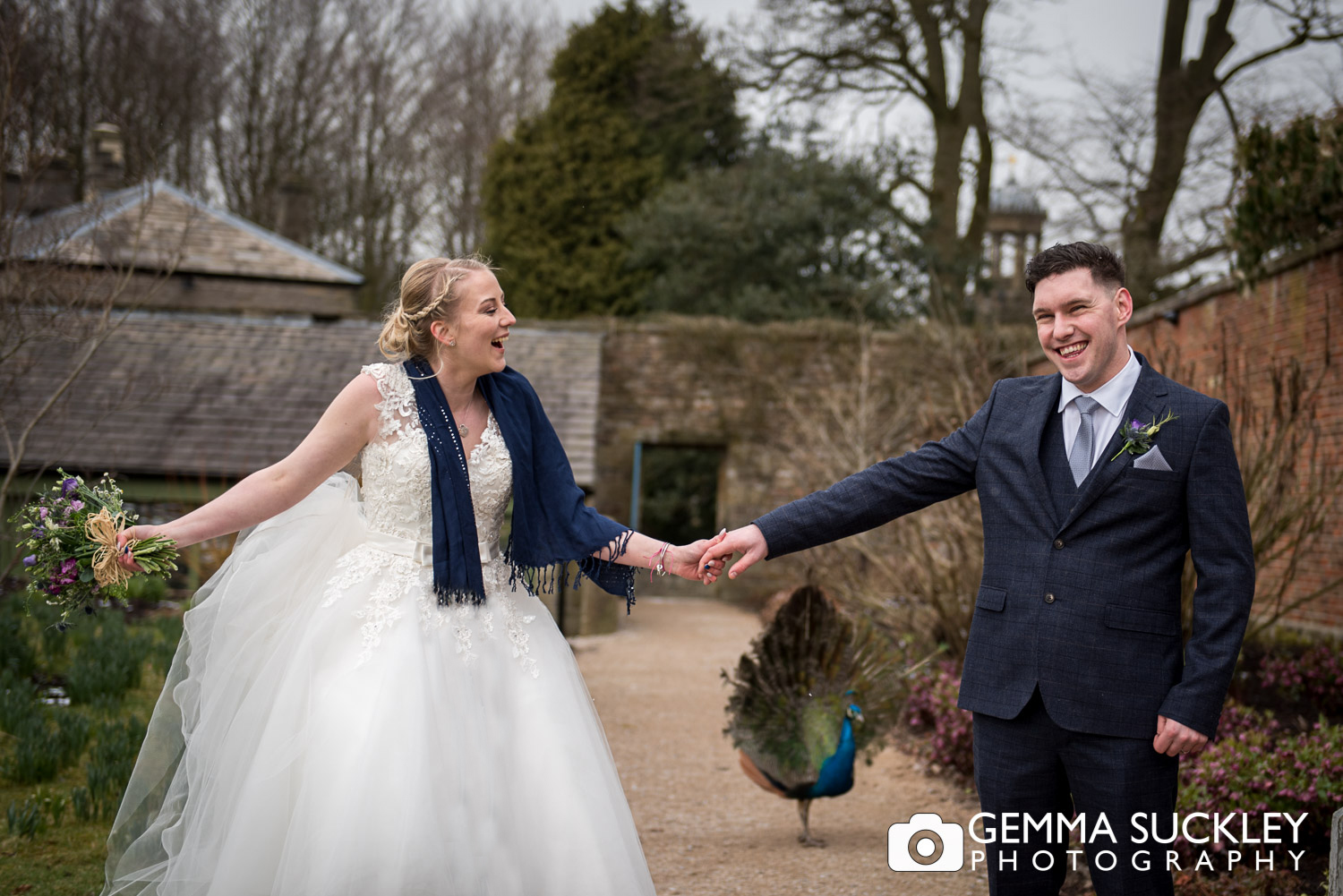 bride and groom at broughton hall with a peacock behind them
