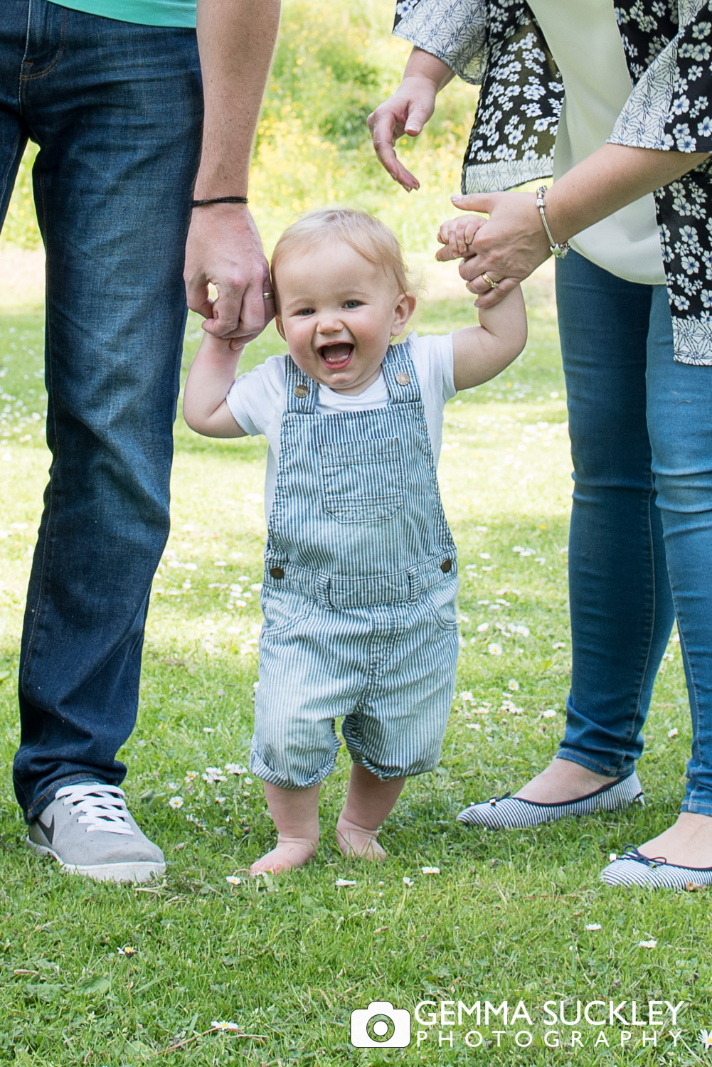baby boy giggling holding his mum and dads hand during a family photo shoot in skipton