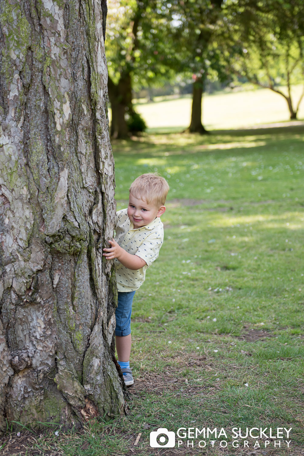 little boy peeking around a tree during a natural family photo shoot in skipton