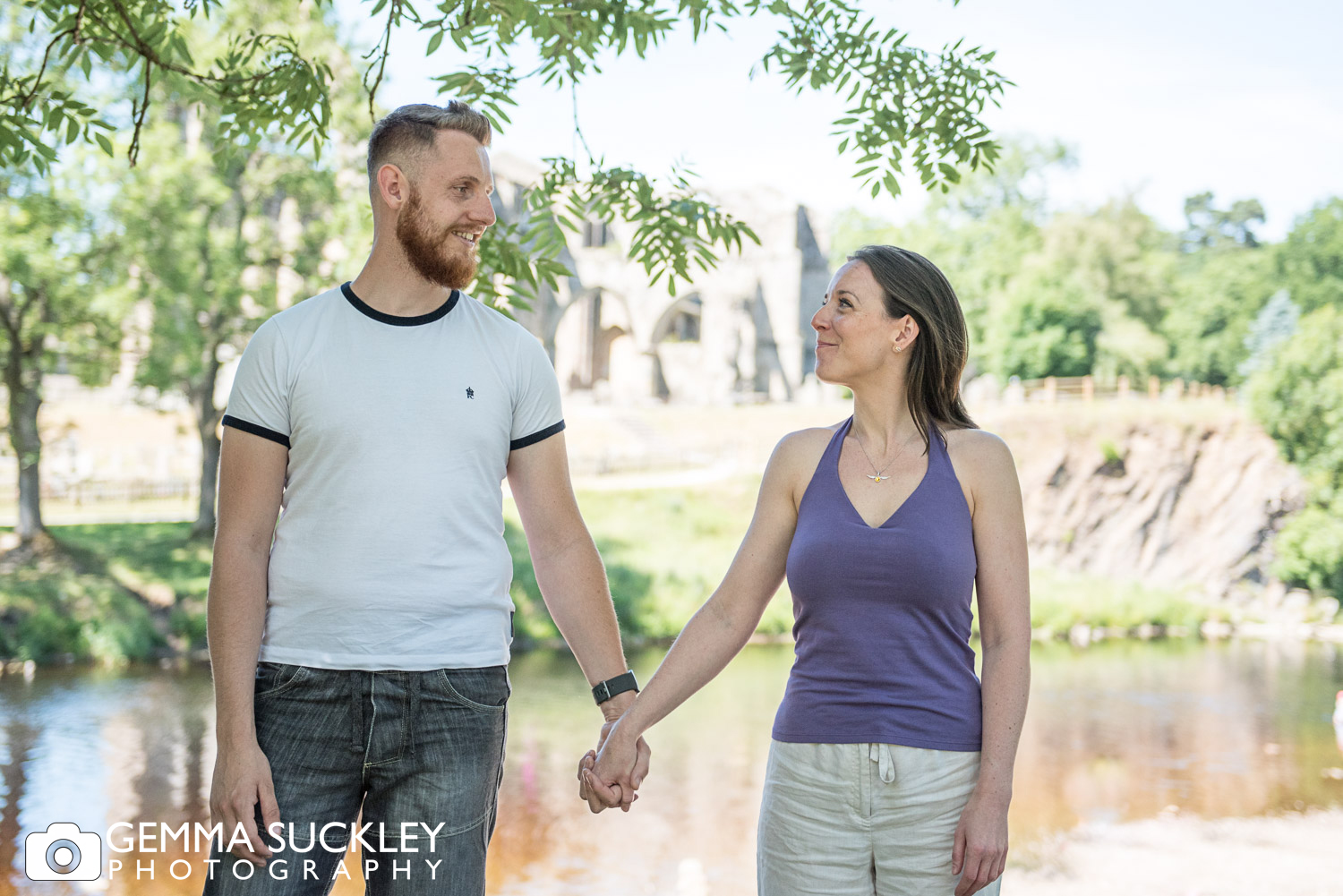 couple holding hands at bolton abbey during a natural family photo shoot