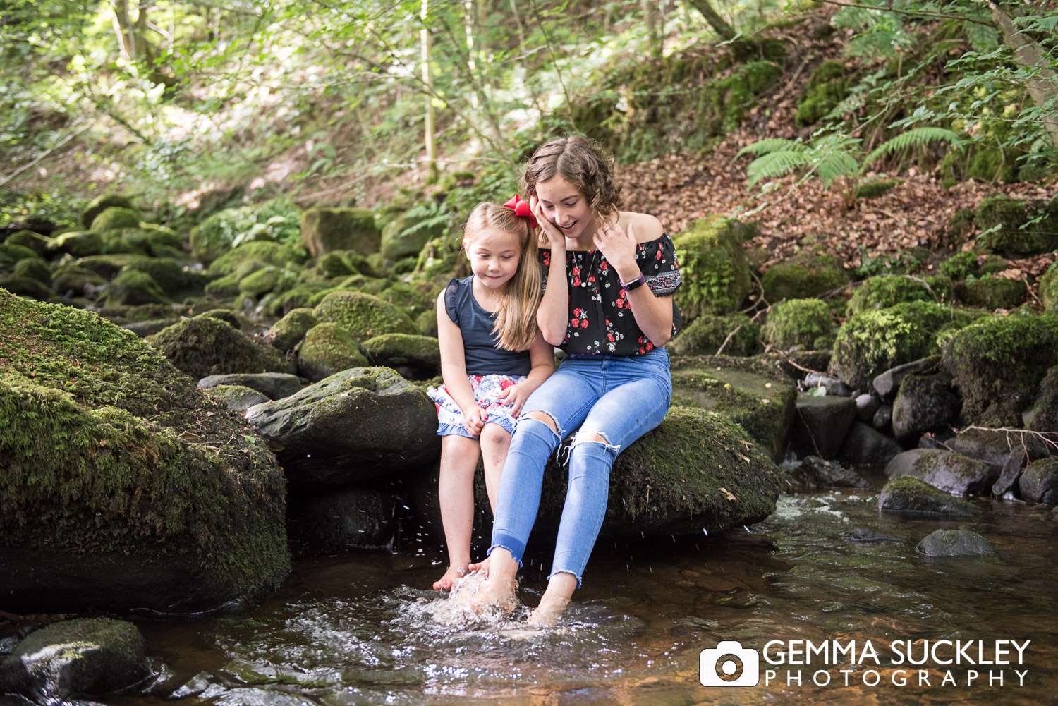 sister dipping their feet in a stream in sutton in craven during their lifestyle photo shoot