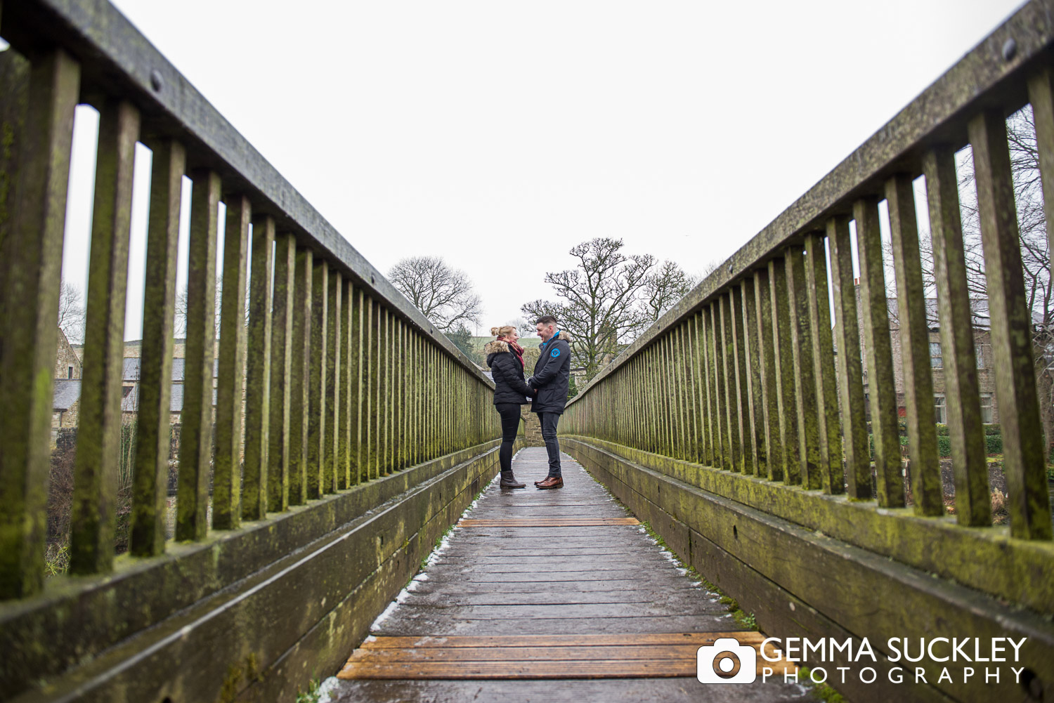 engaged couple holding hands on Linton Bridge during their engagement photo shoot