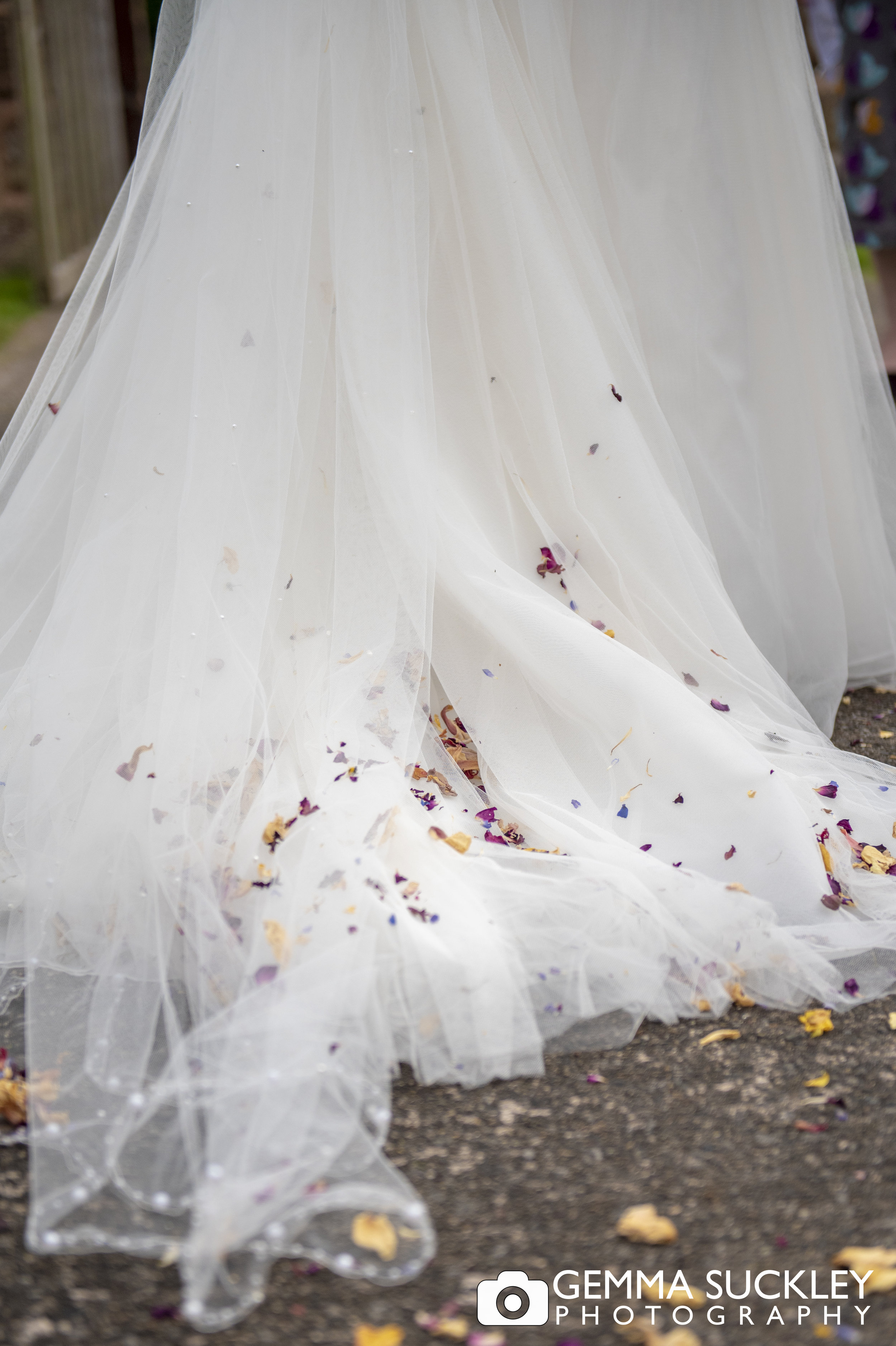 close up photo of confetti on the back of a wedding dress