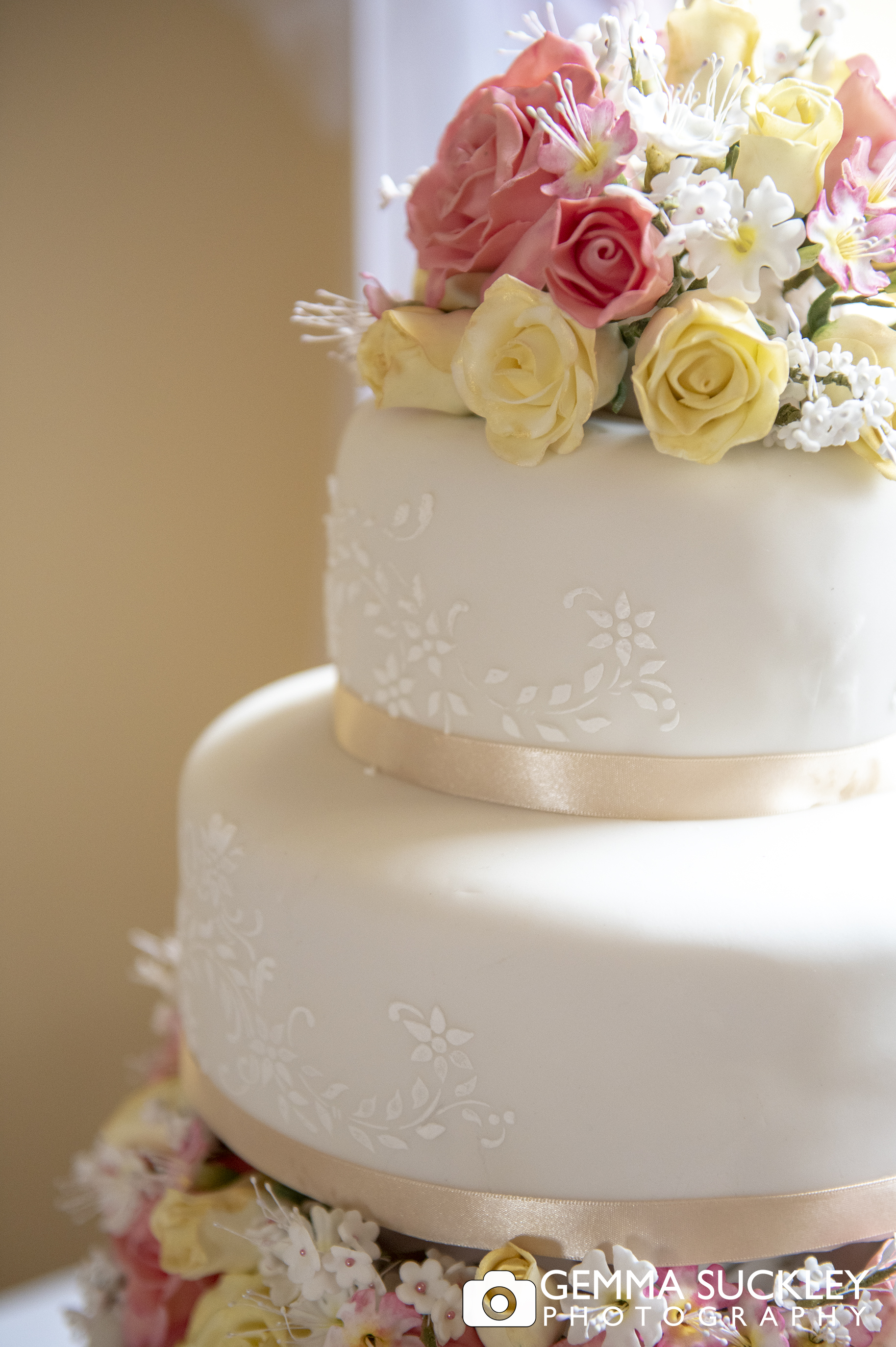 close up photo of a wedding cake topped with flowers