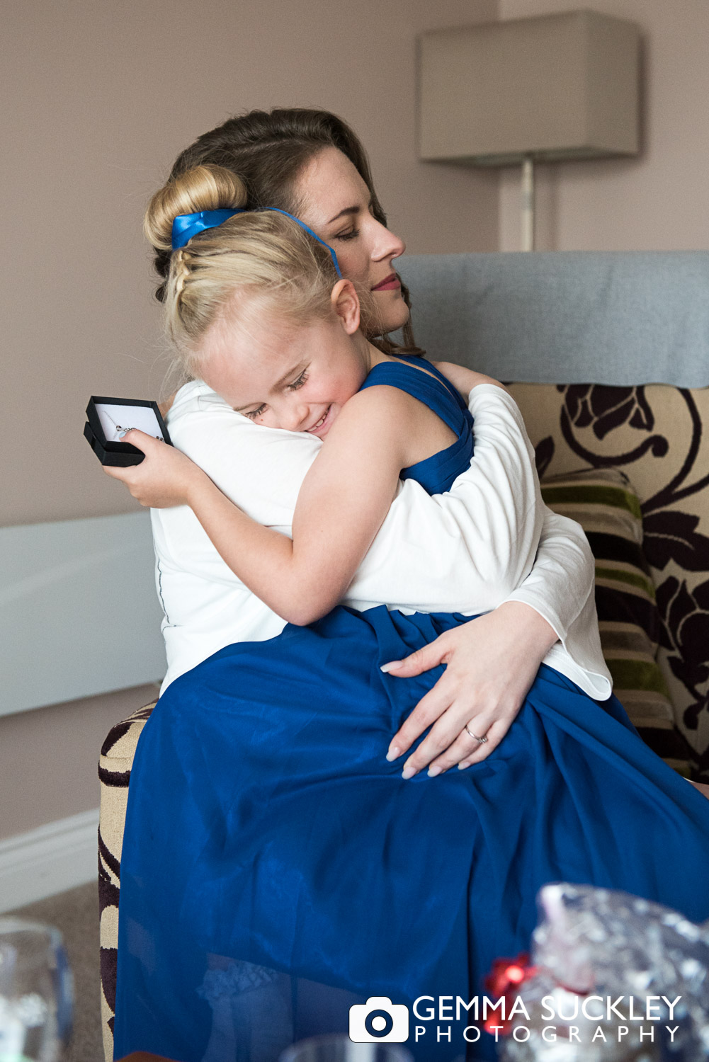 flower girl sitting on the brides knee hugging during bridal prep at coniston hotel in skipton