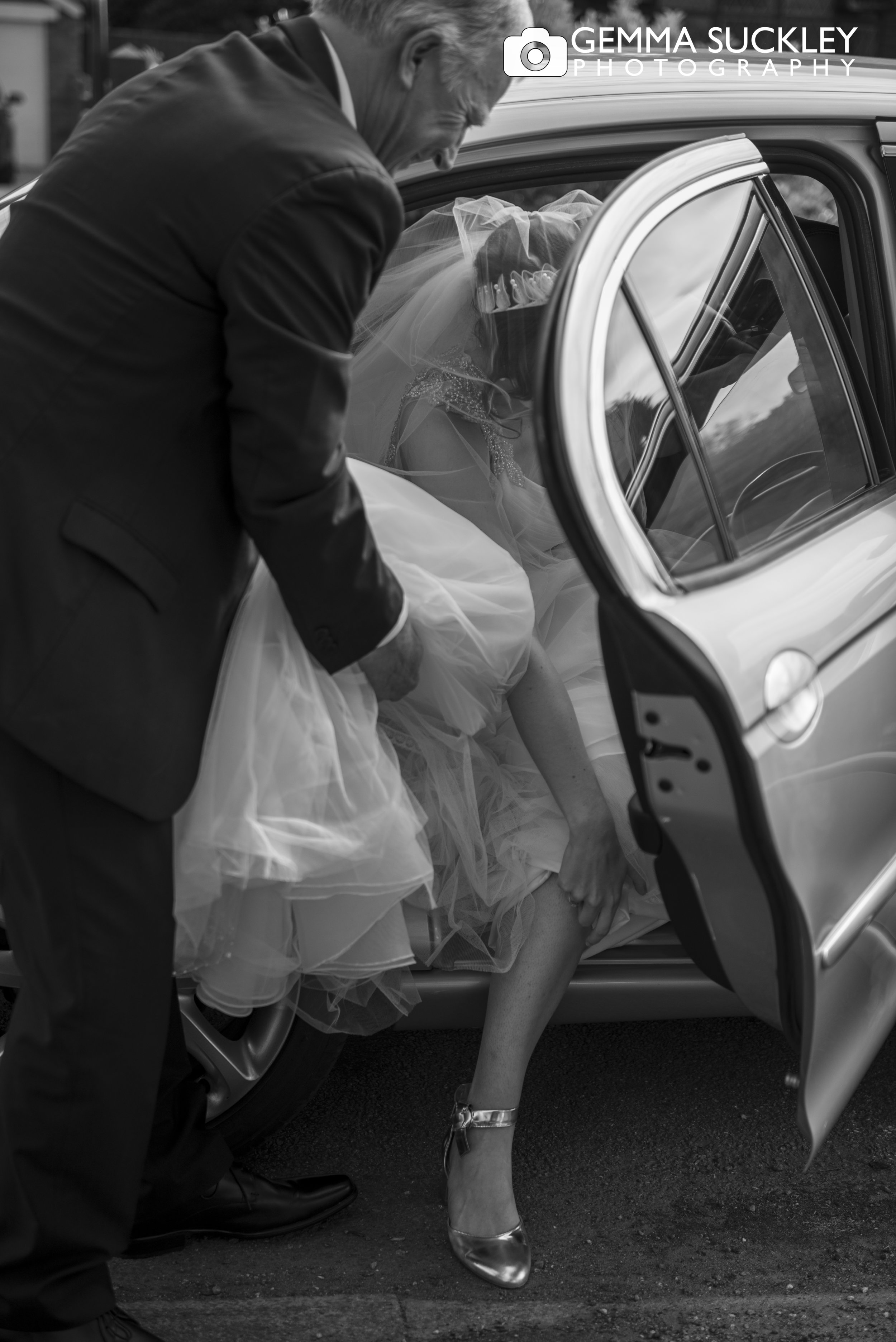 black and white photo of bride getting out of the car on arrival to the church