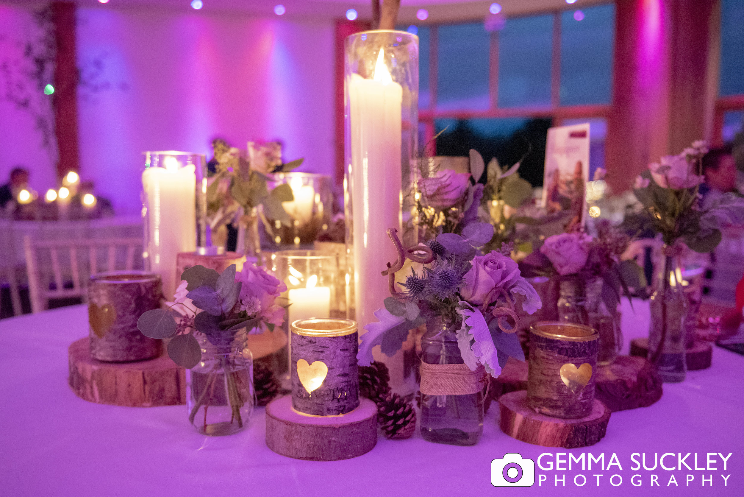 candles and flowers on the table at the outbarn wedding in clitheroe