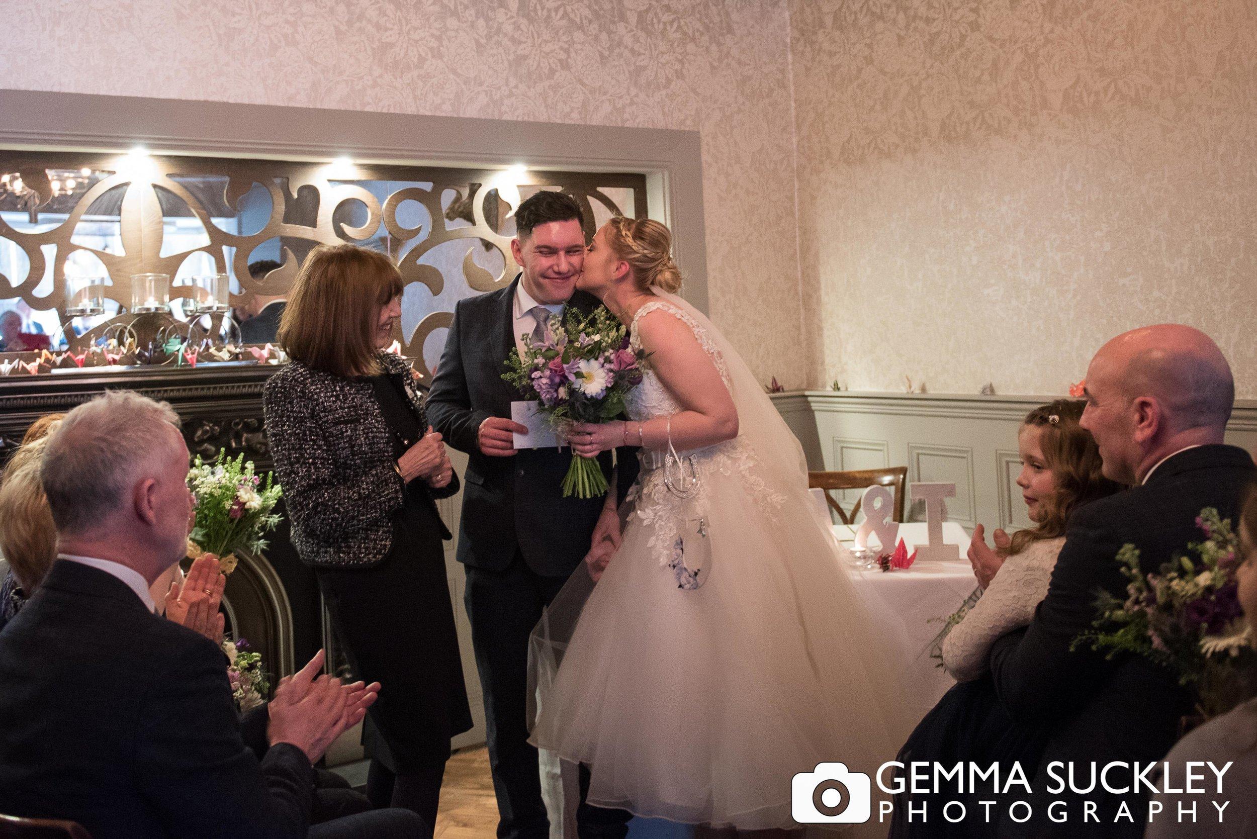 bride kissing the groom just married