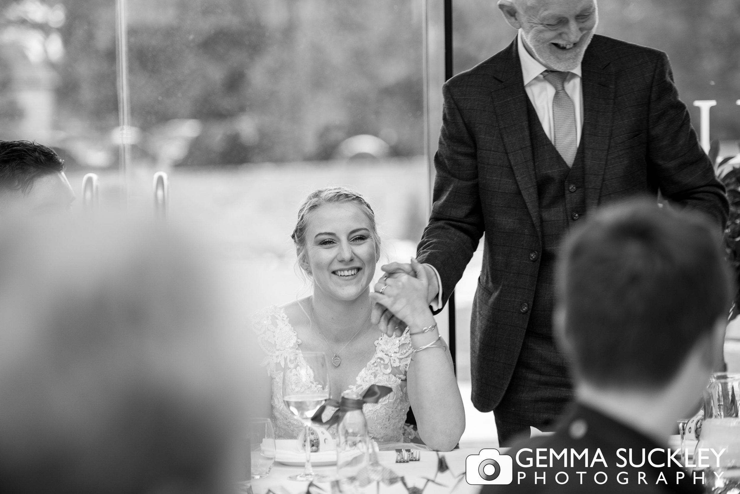 bride holding her dads and during wedding speeches at utopia
