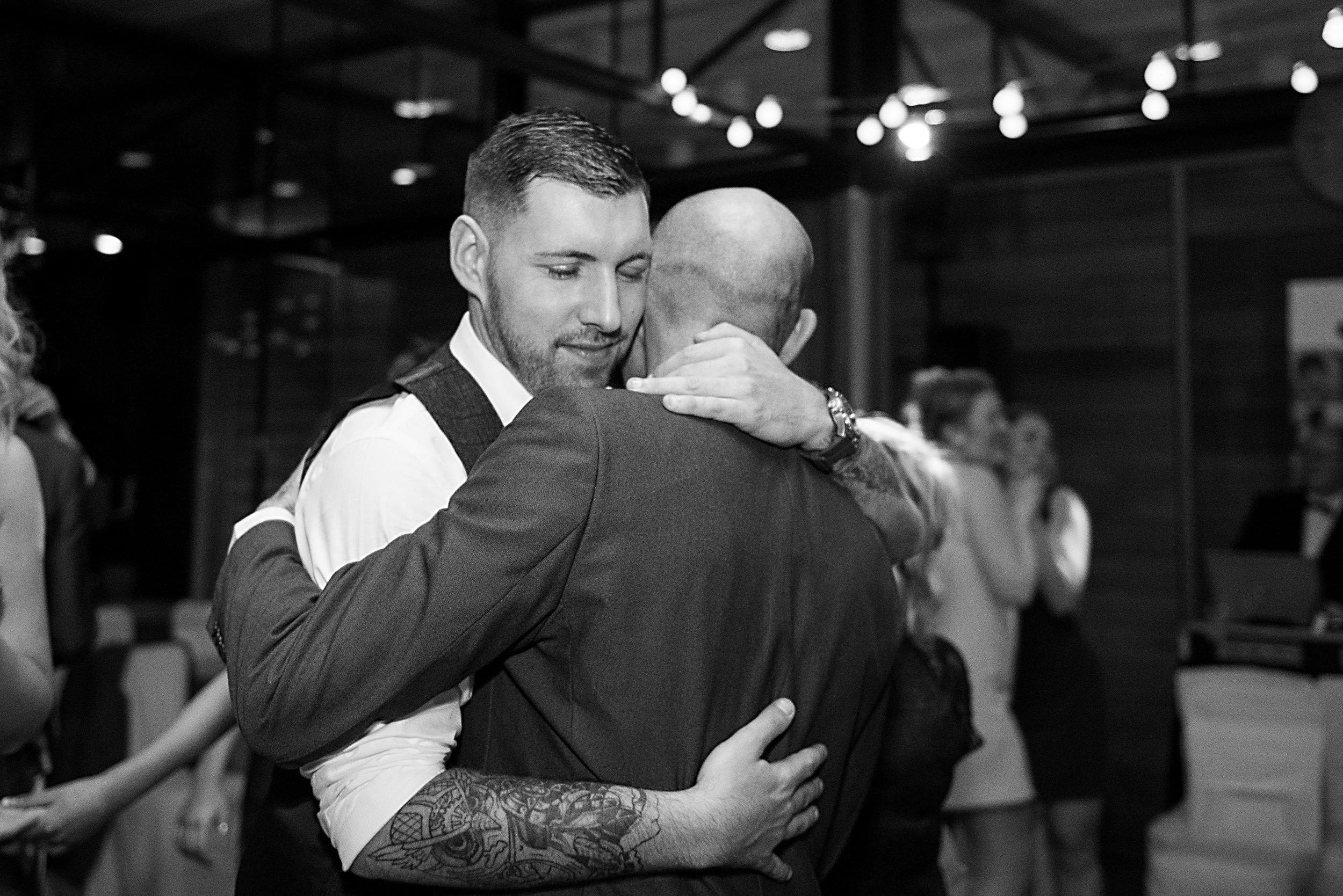 groom hugging his dad at utopia wedding reception
