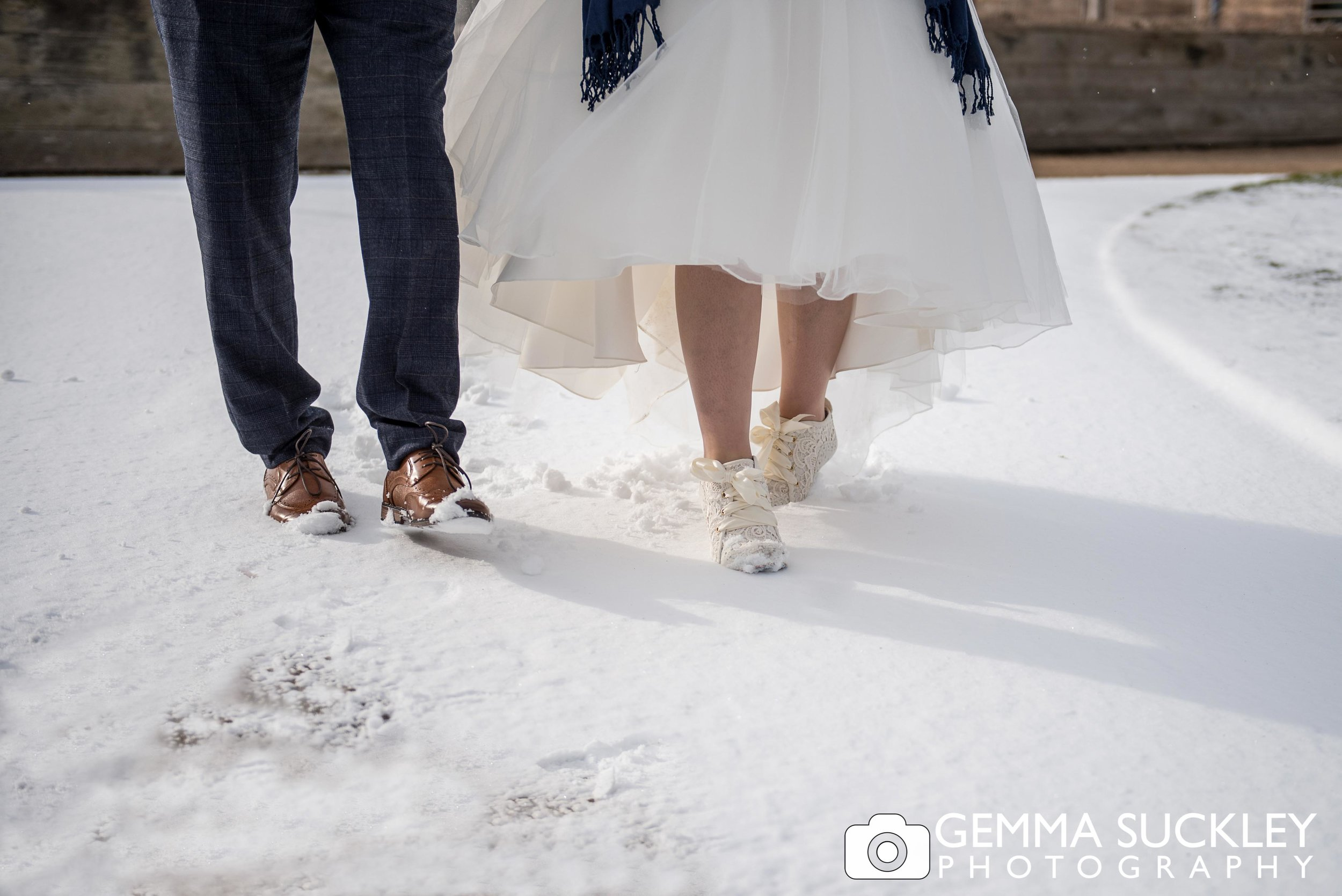 bride and groom walking in the snow at brought hall wedding