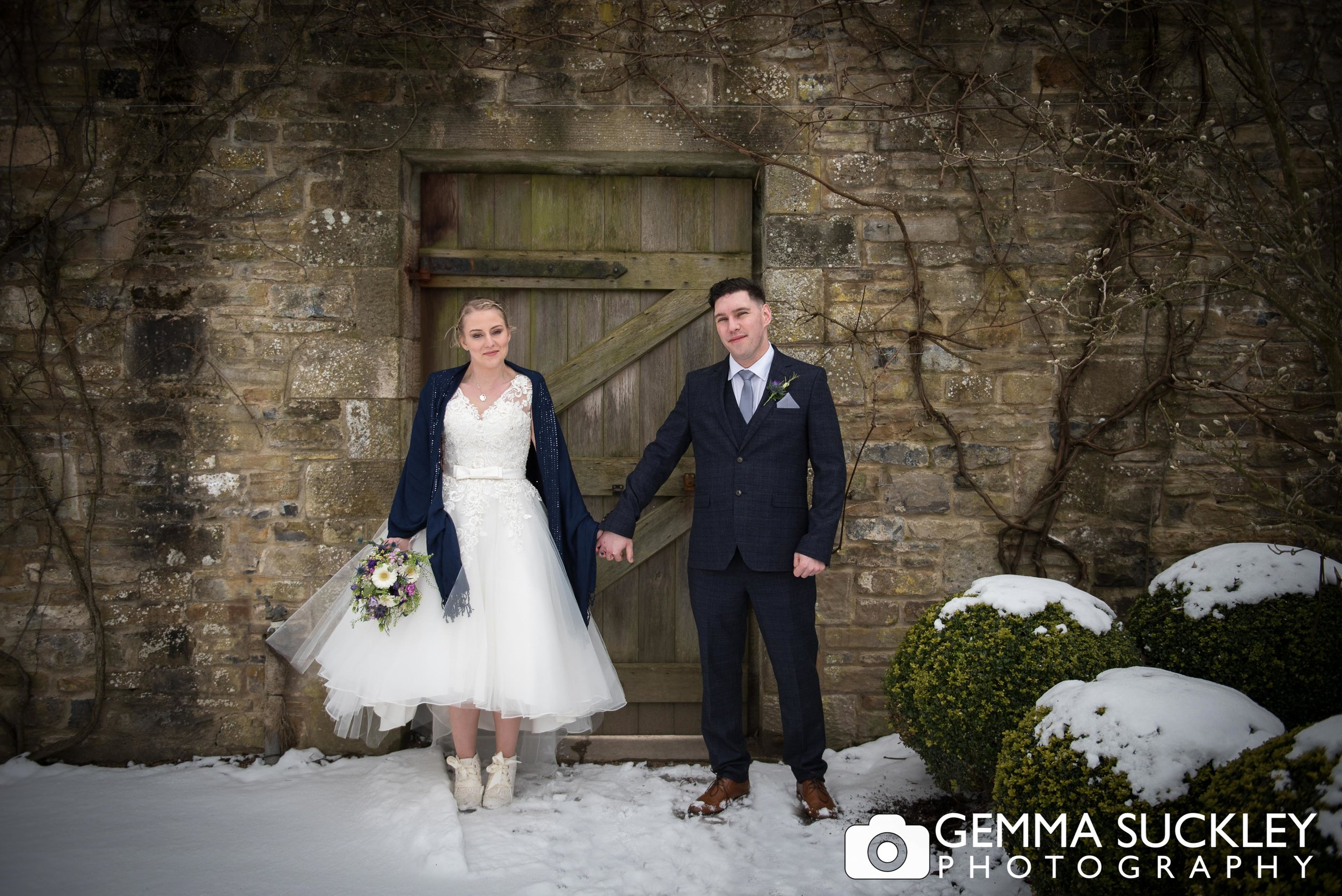 bride and groom holding hands at broughton hall