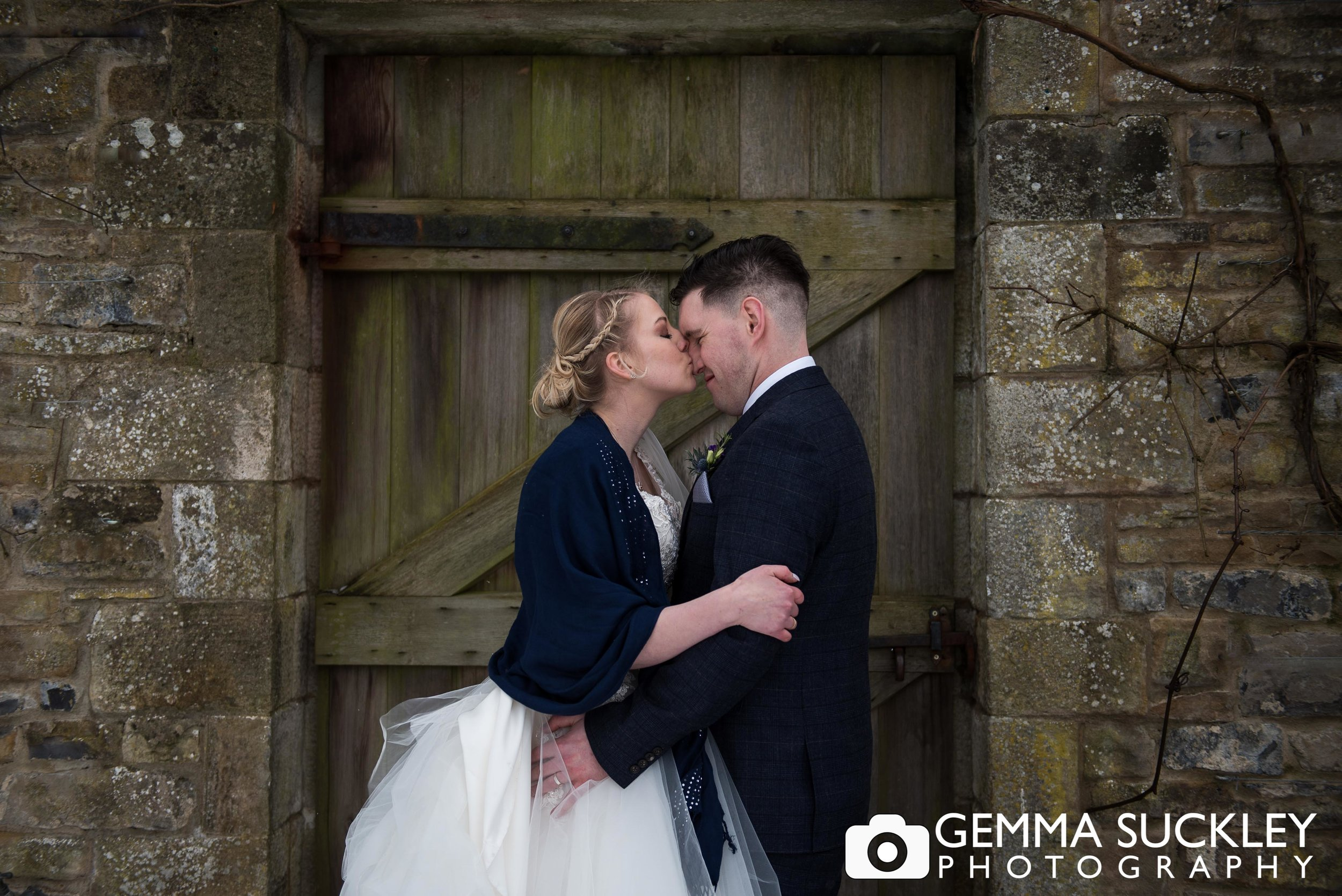 bride kissing groom at utopia at broughton hall