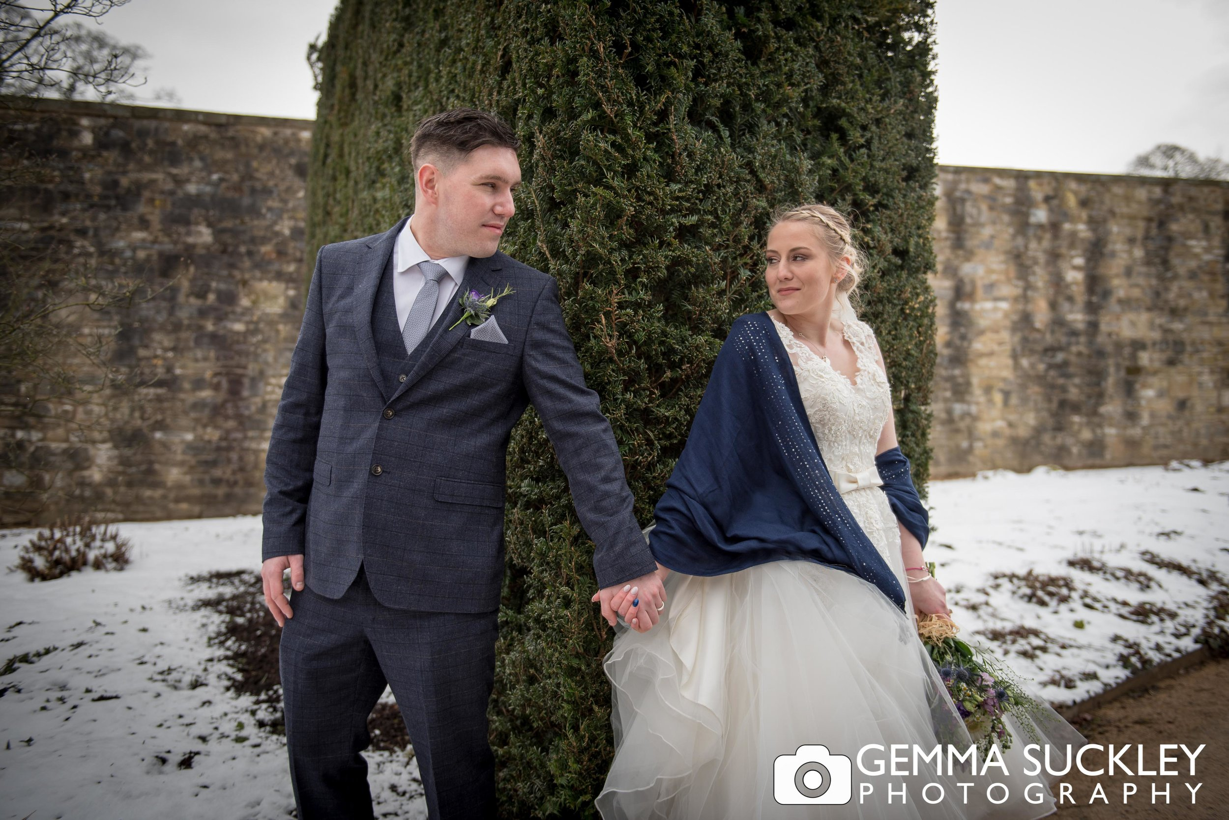 snowy wedding photos of bride and groom at broughton hall