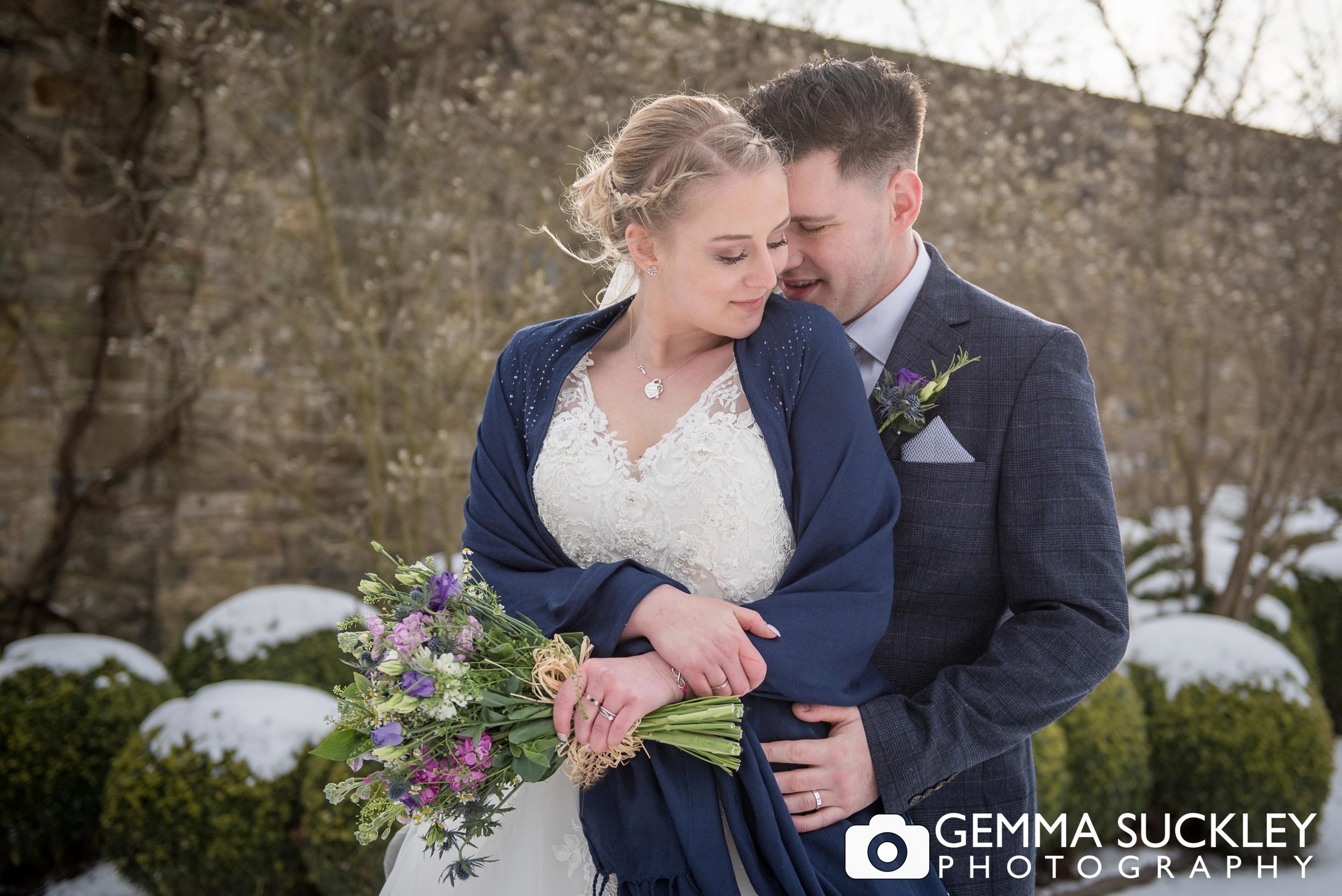 bride and groom hugging in the snow at broughton hall