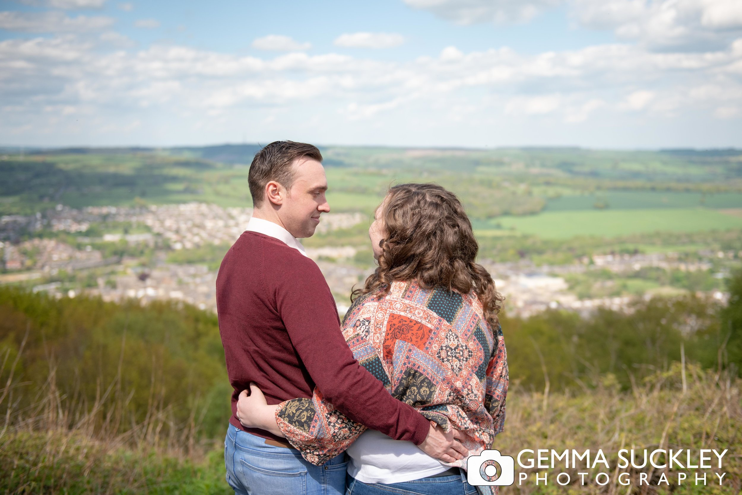 engaged couple looking out the view from the otley chevin