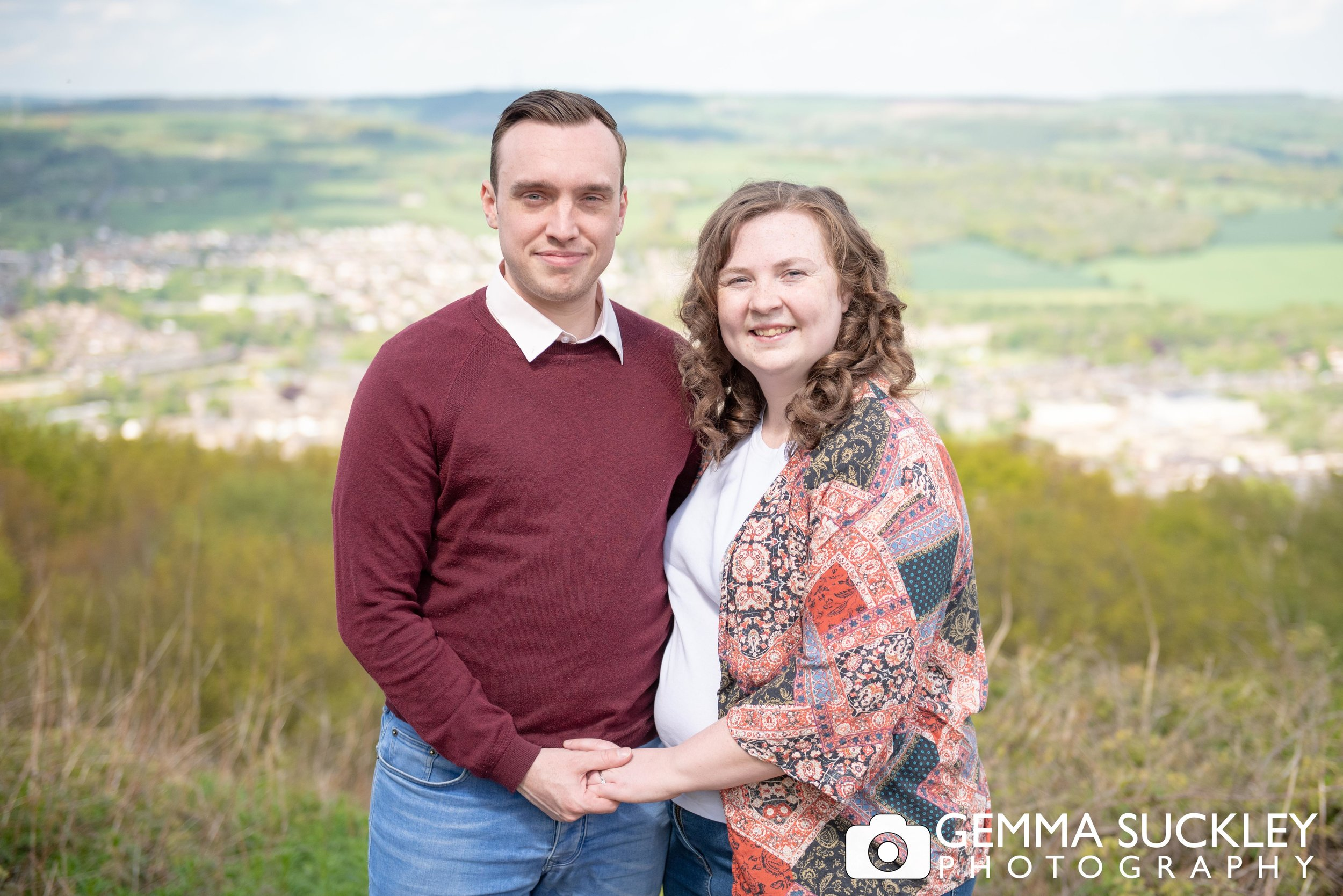couple holding hands and smiling during their engagement shoot in otley