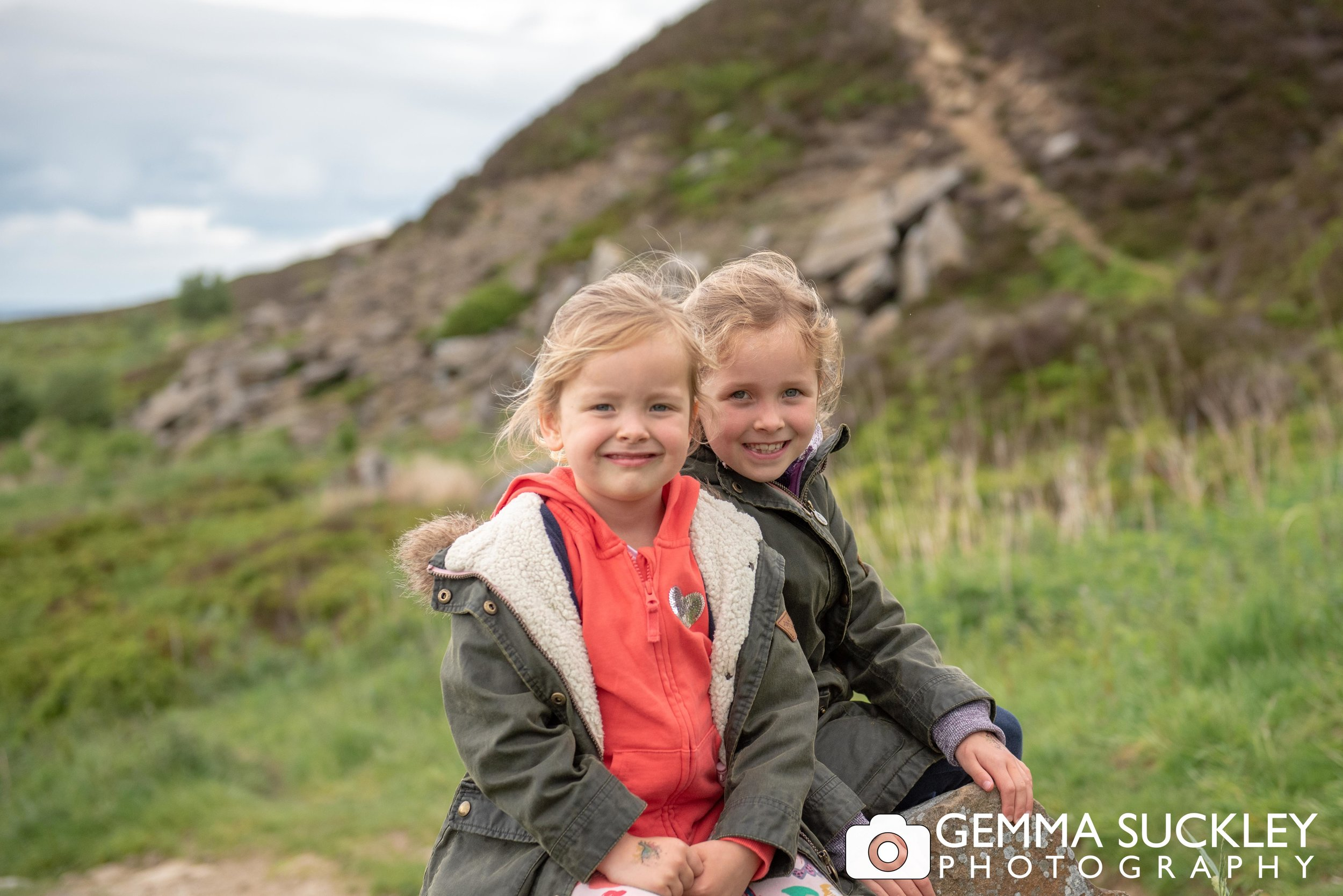 two little girls smiling for a family photo on hawotrh moor