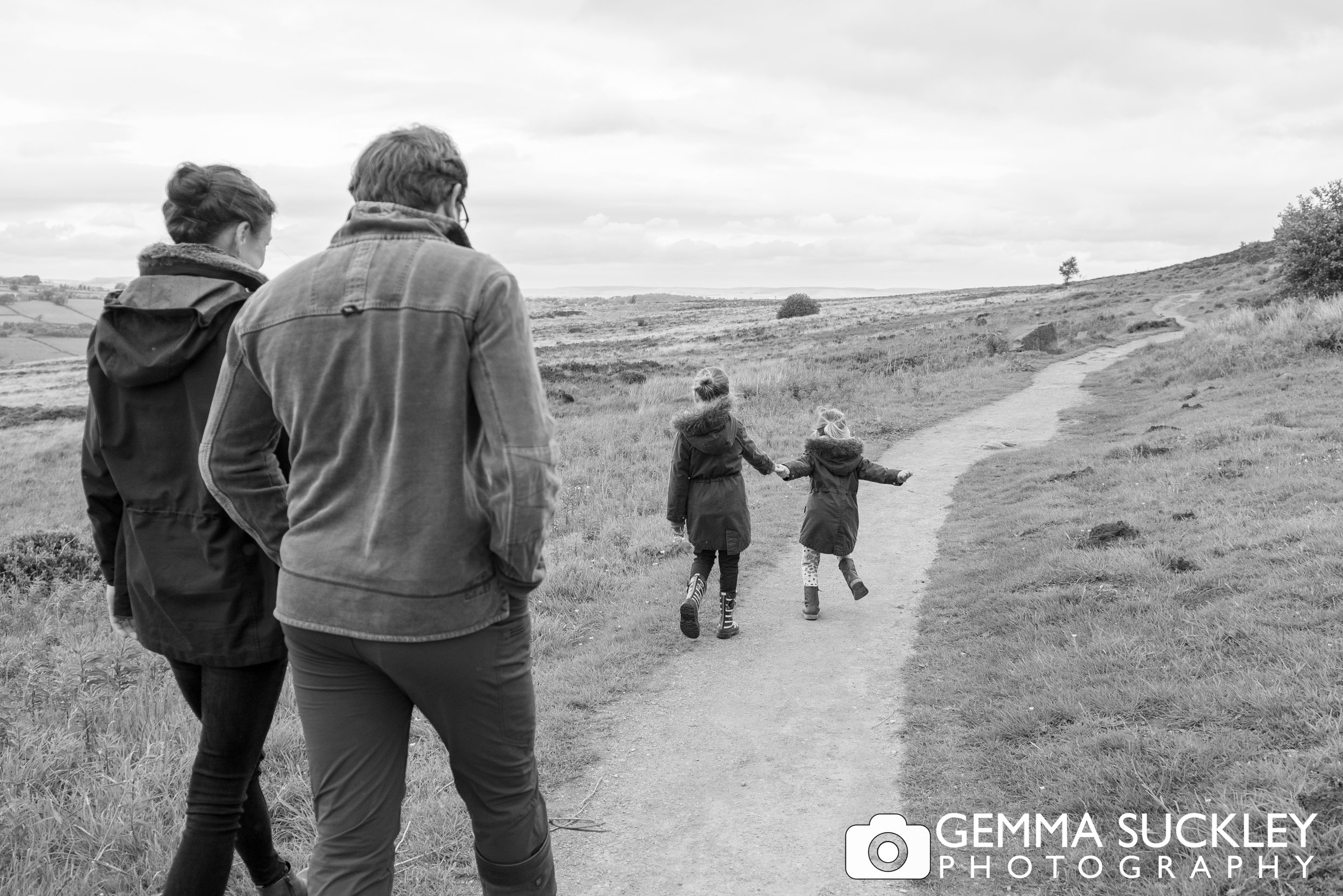 black and white photo, naturally capturing a mum ans dad walking with their kids running ahead