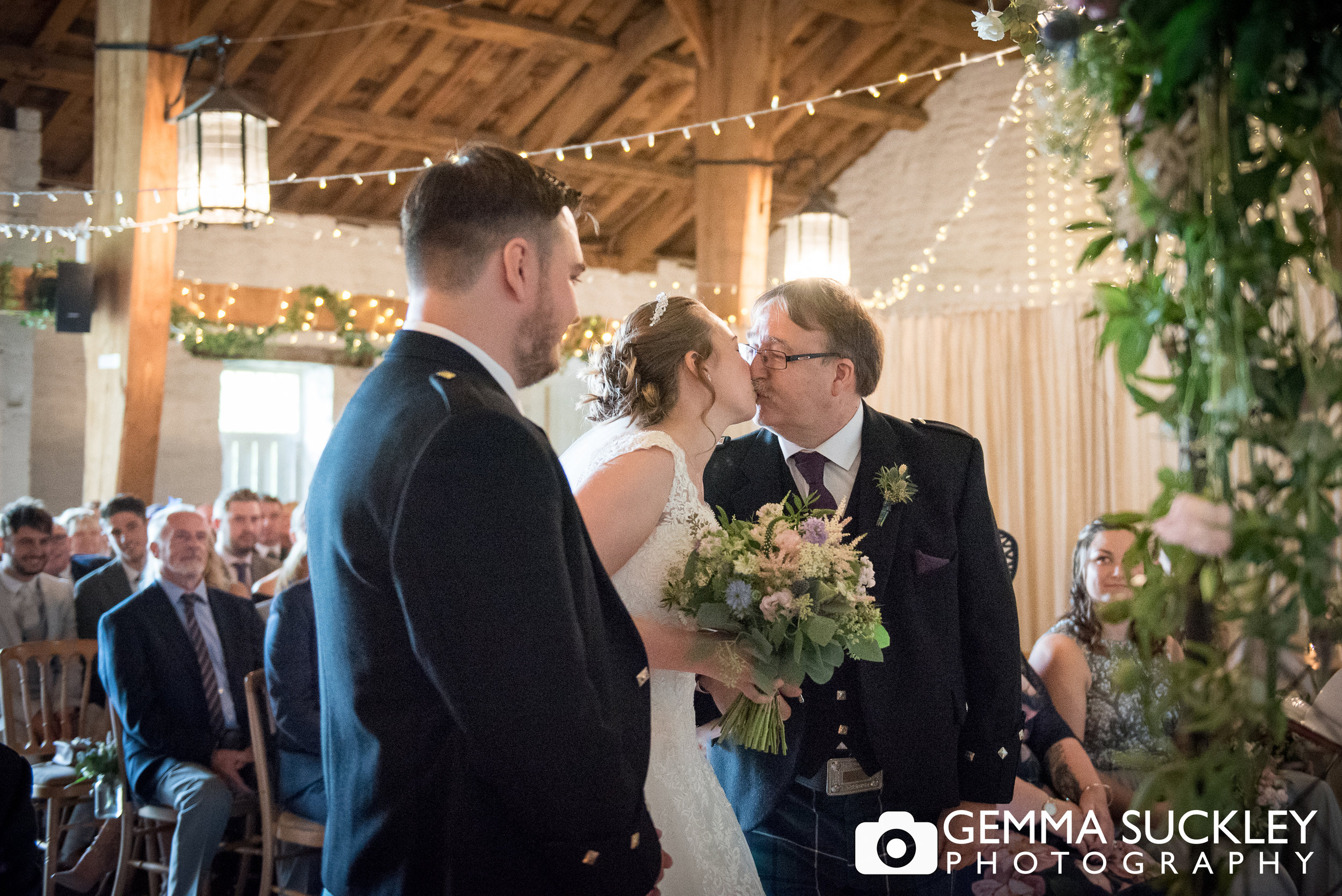 father of the bride kissing his daughter at east riddlesden hall