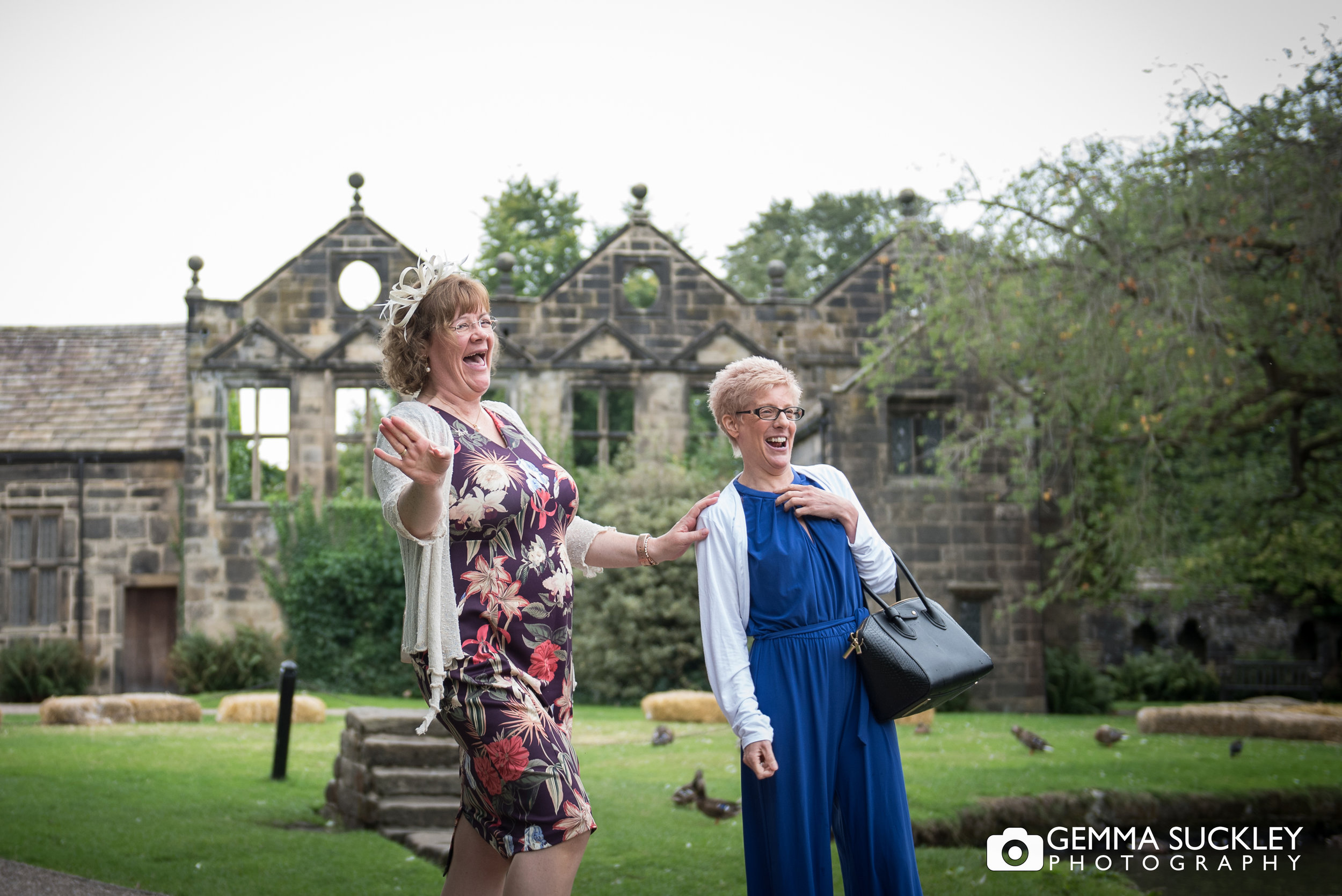 wedding guest laughing with east riddlesden hall in the background
