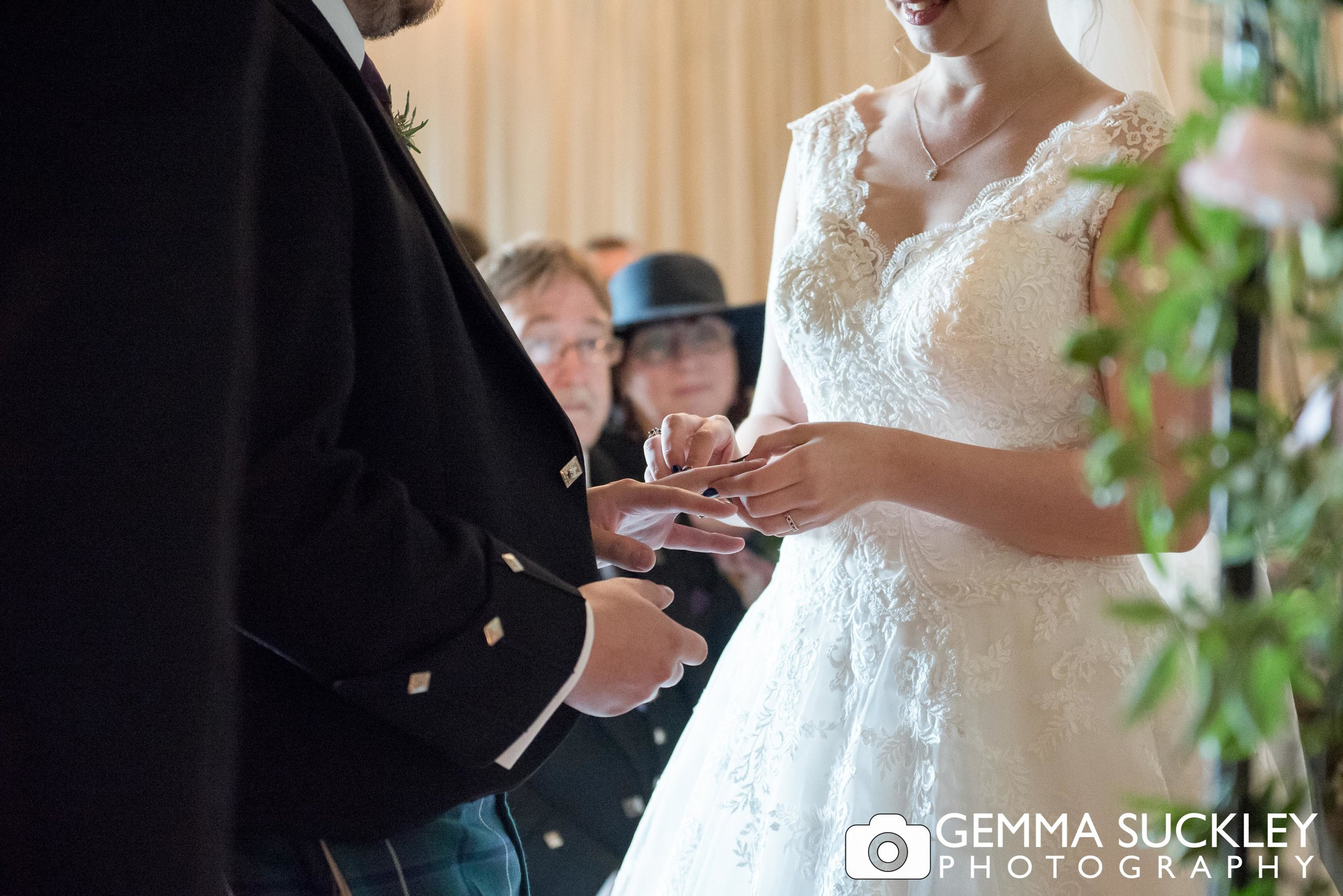 groom placing the ring on his bride's finger