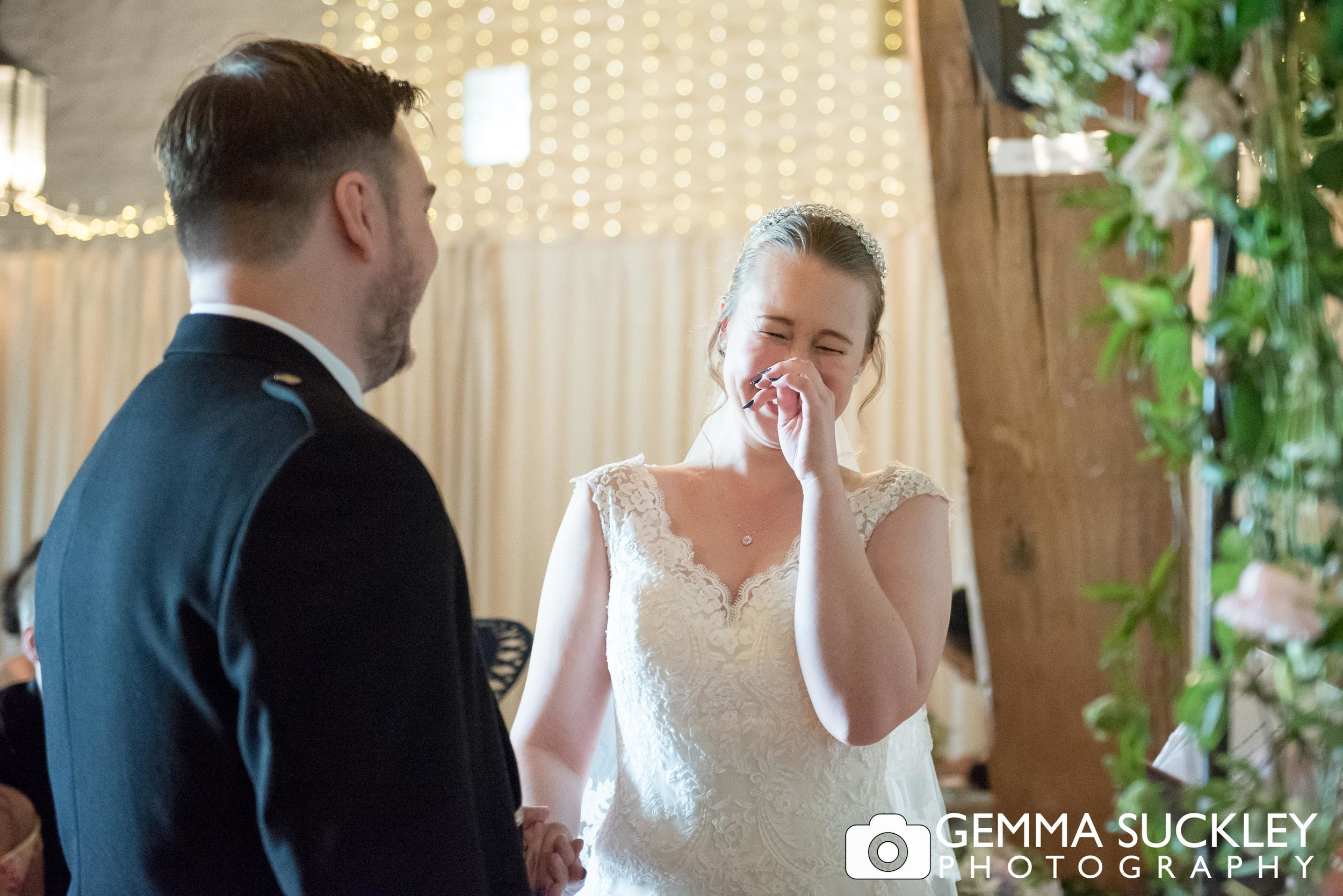 bride laughing during her wedding vows