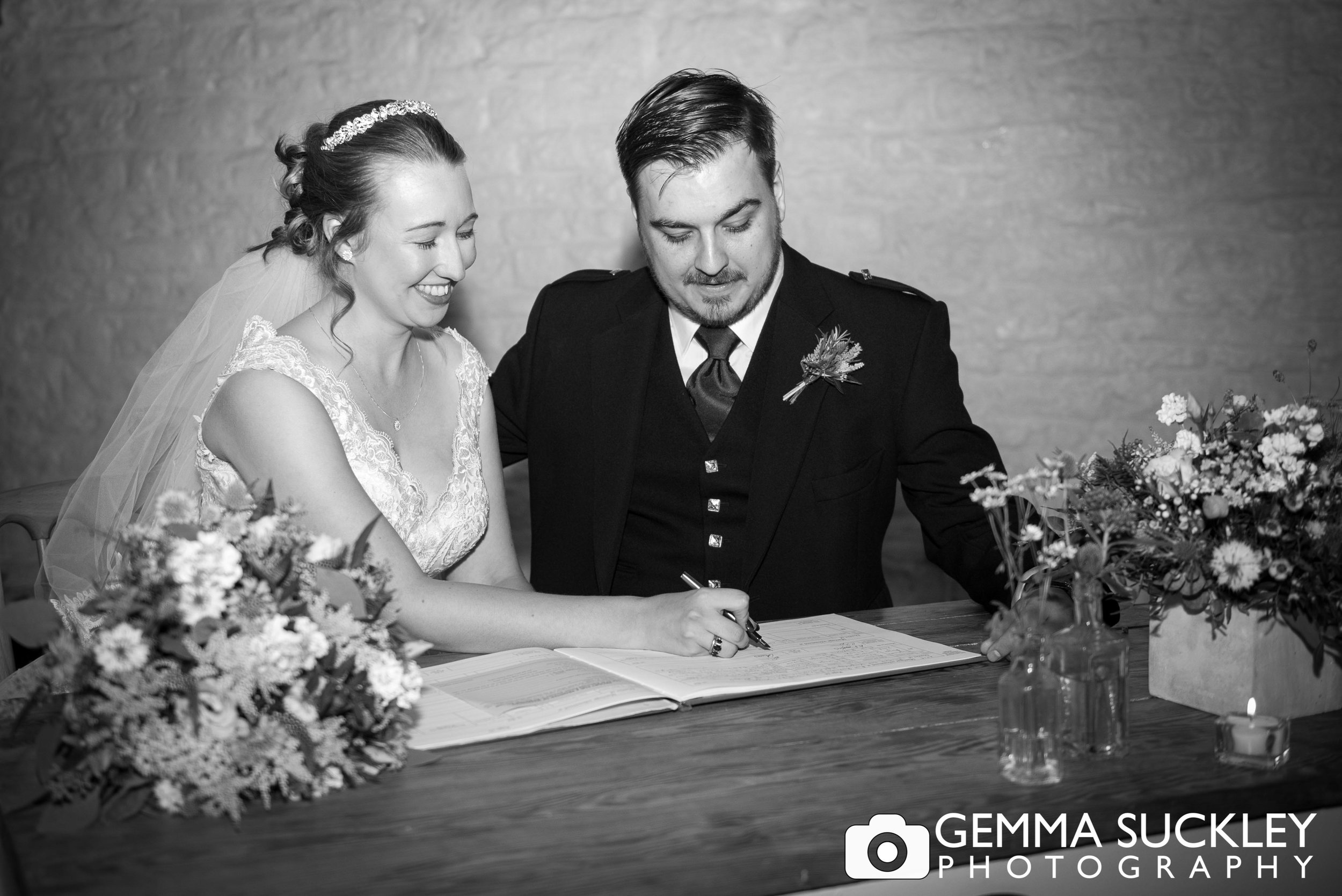bride and groom signing the register at east riddlesden hall