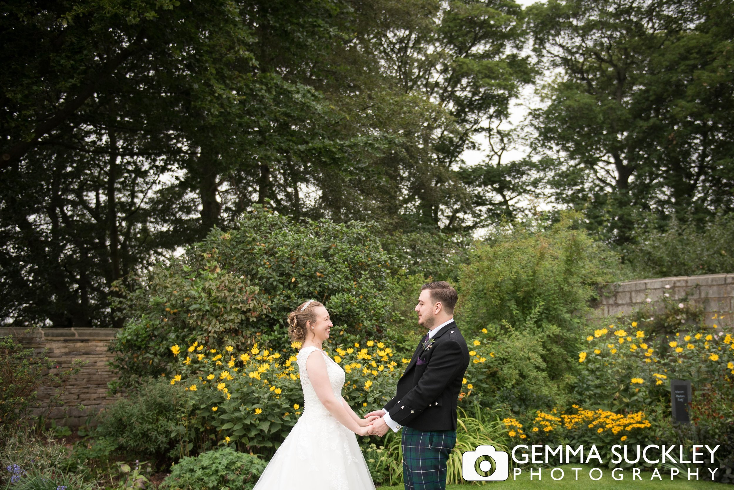 bride and groom in the flower garden at east riddlesden hall