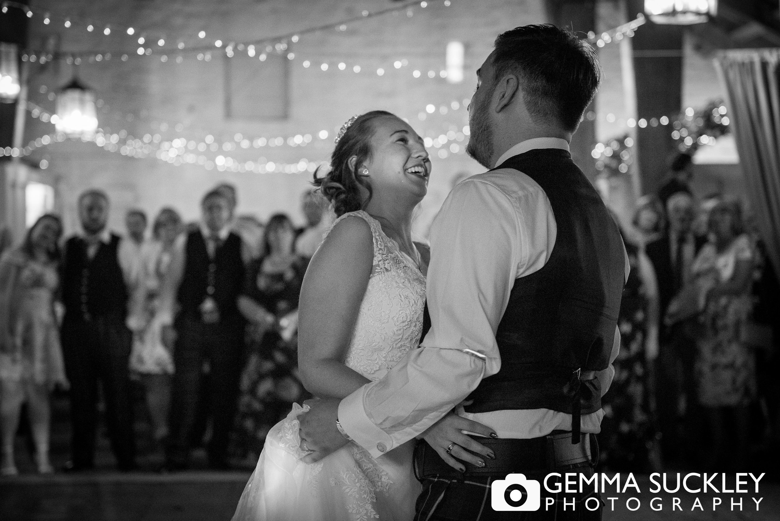 black and white photo of bride and groom dancing at east riddlsden hall